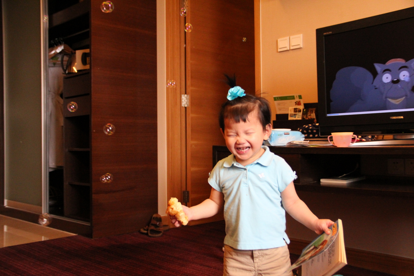 Blowing bubbles in the hotel room. (She usually needs to have something in each hand to feel safe).