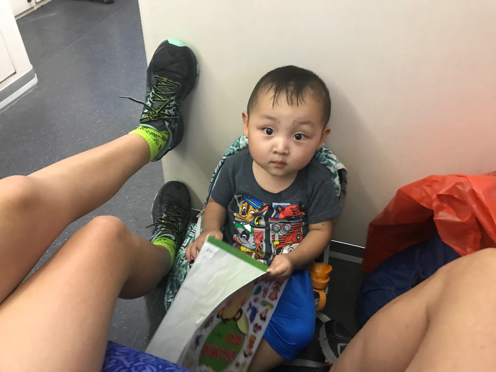 Luke made himself a seat out of Abigail's backpack on the floor of the train to Hong Kong.
