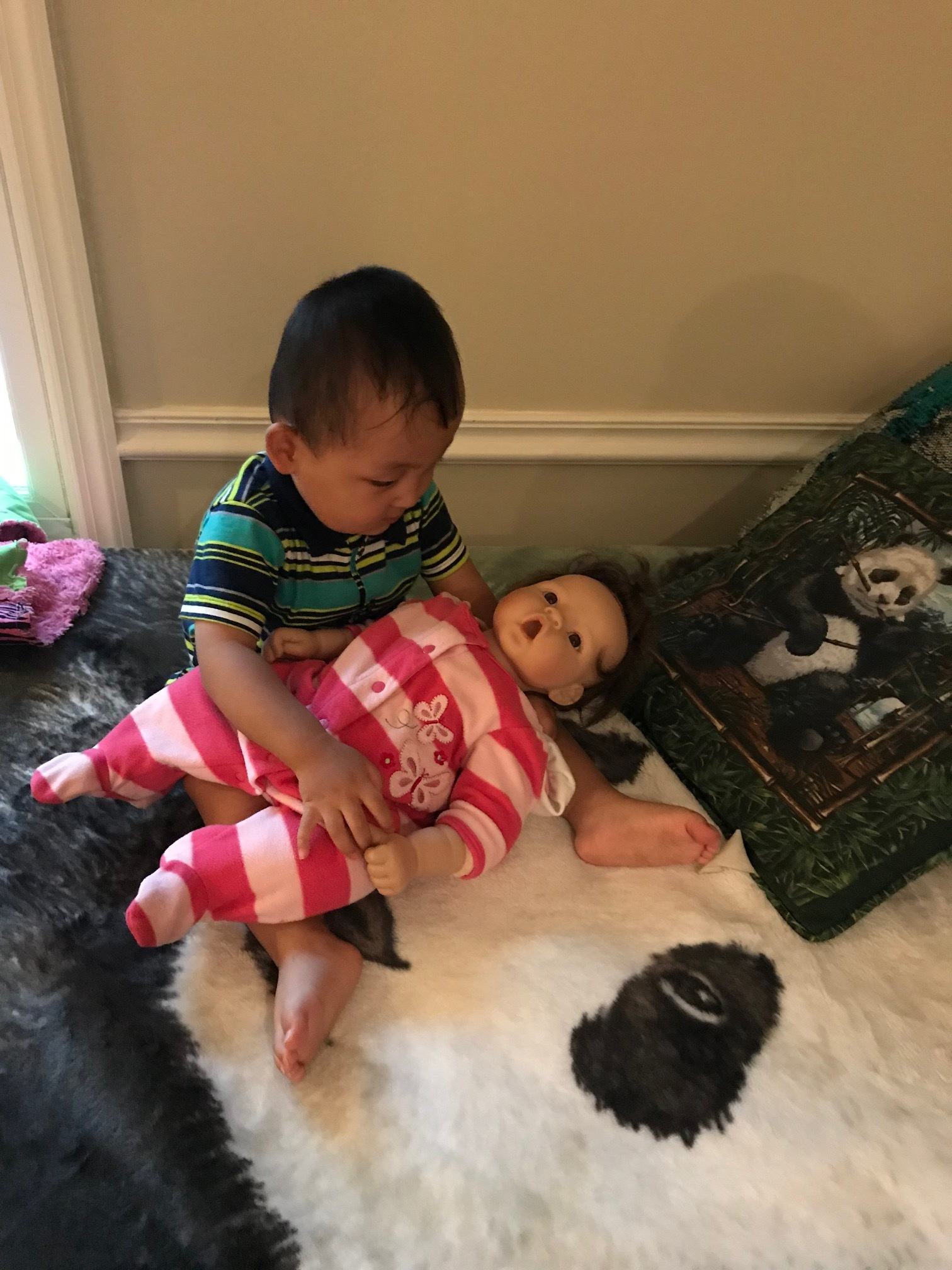 Playing with his sister's doll