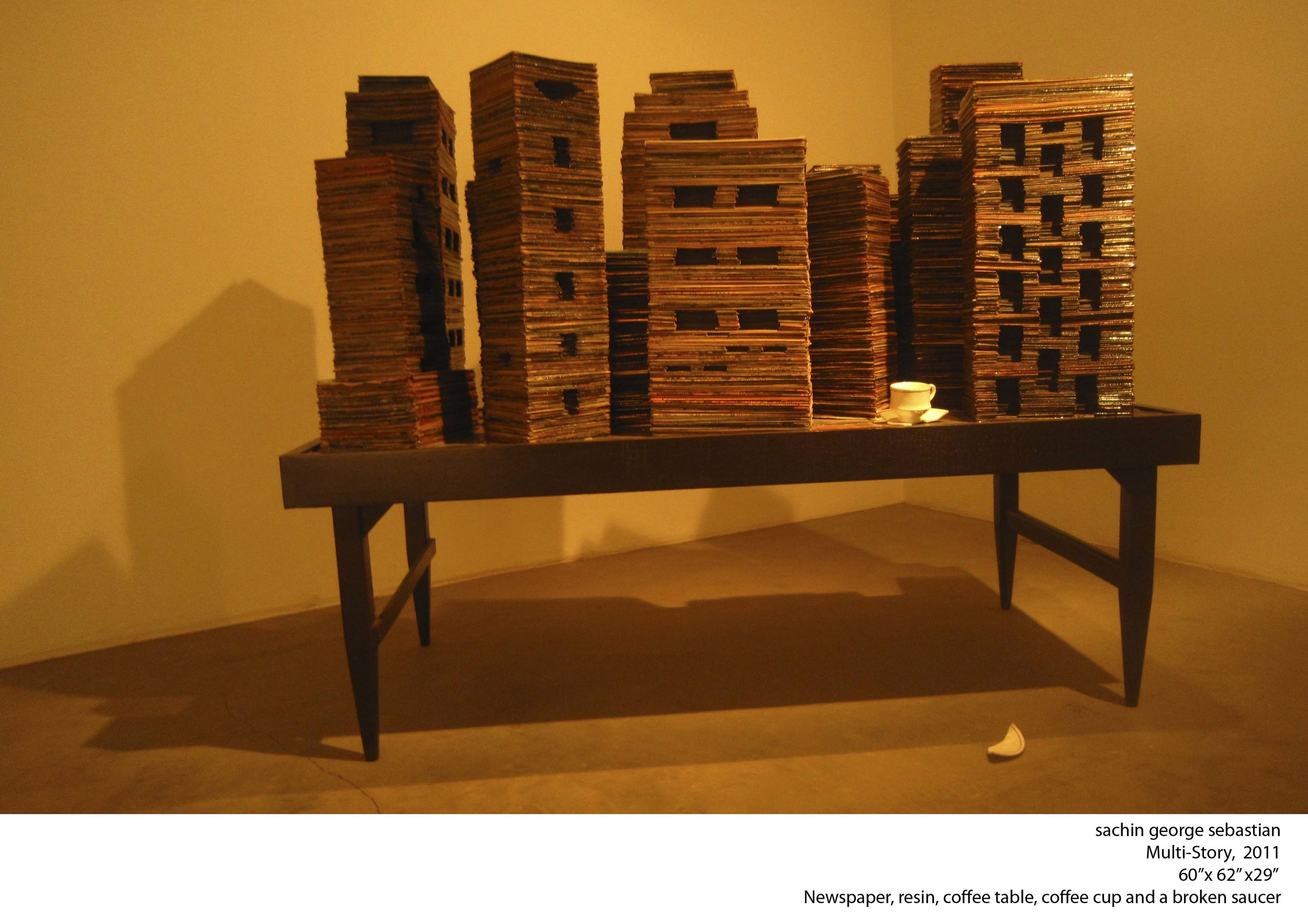sachin george sebastian, 2011, Multi-story,60x62x29 inches, newspaper stacks, resin, cofee table, cup and saucer.jpg