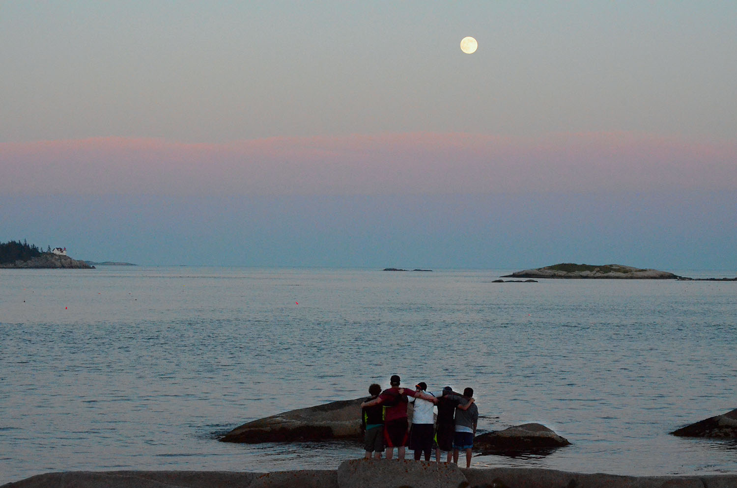Students enjoy a quiet moment as the full moon rises over Heron's Neck lighthouse