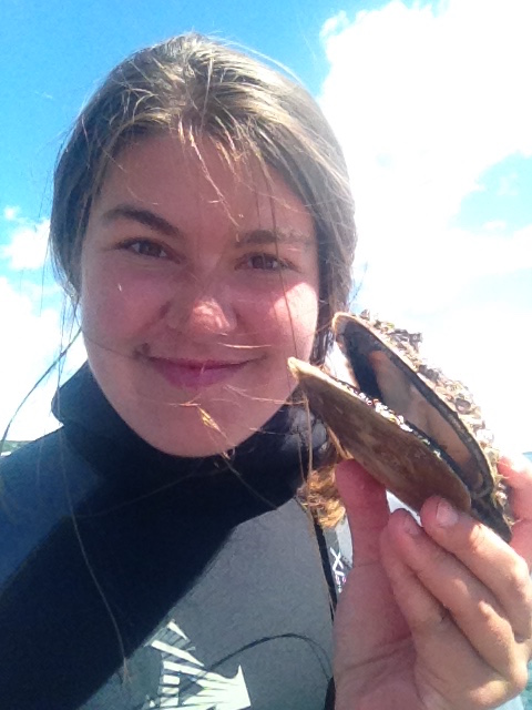 Research Assistant Bailey Moritz posing with a scallop