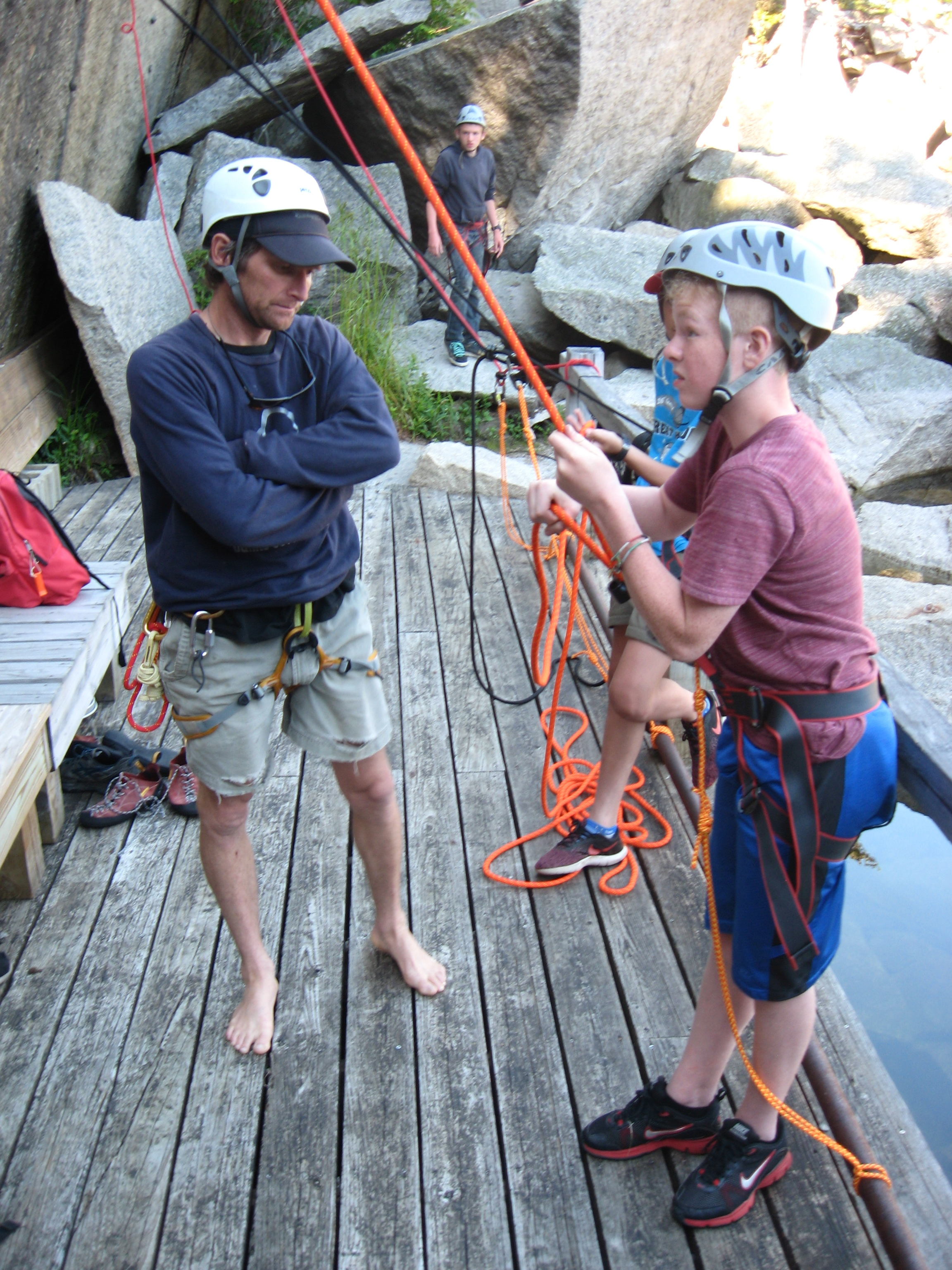 Facilities director and climbing guru Sam Hallowell looks on as the boys rock climb and belay.