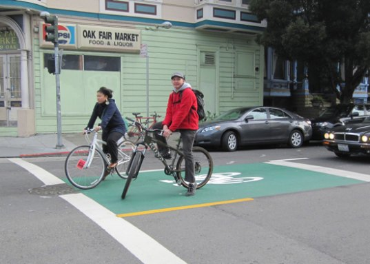 Bike boxes or advanced stop bars, like this one in San Francisco, let people on bikes pull in front of cars at intersections to increase visibility.