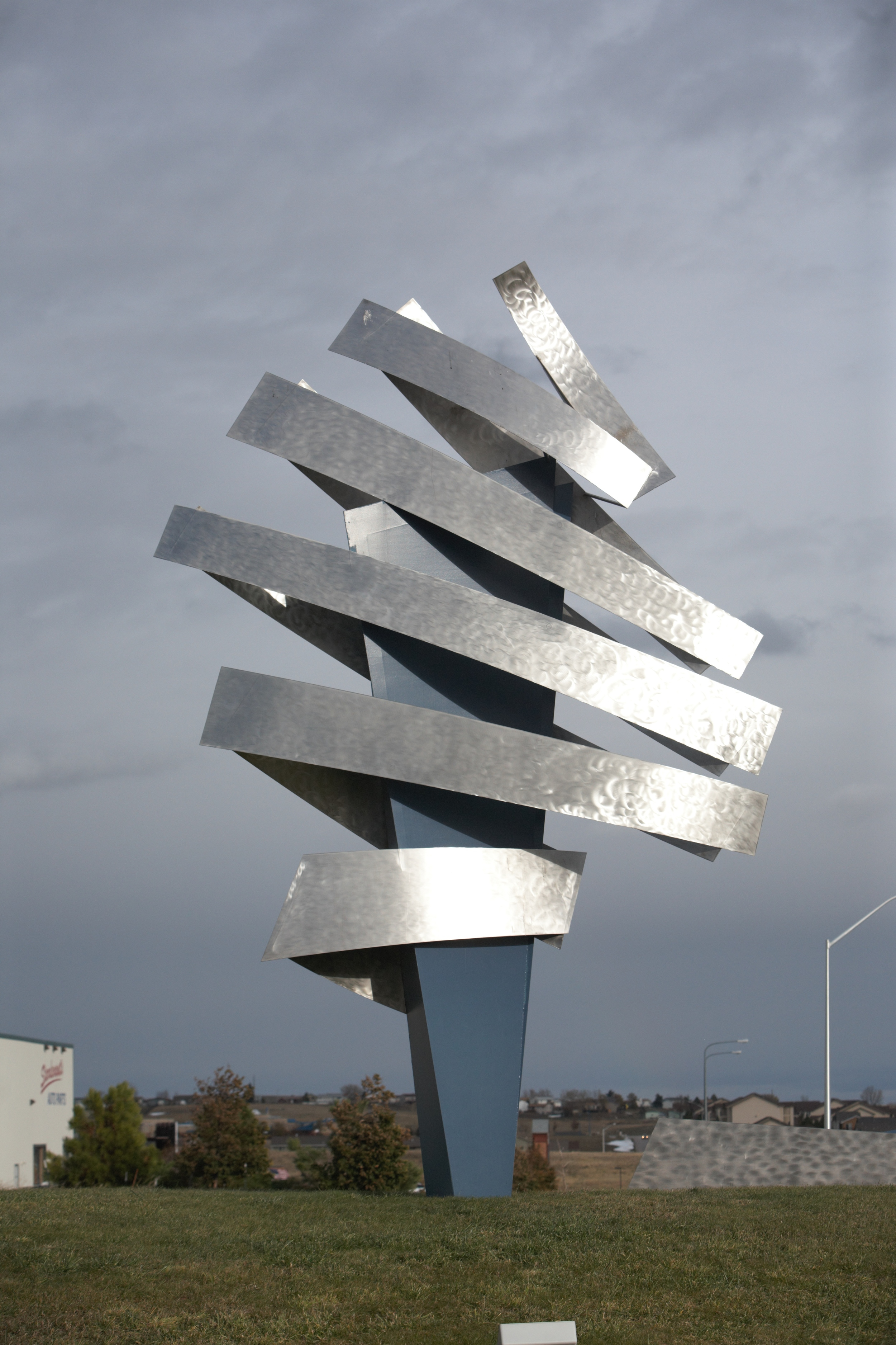 """Created by internationally renowned artist Dale Lamphere, """"Digital Mercury"""" is the symbol of Fenske Media business model. 'Mercury', the messenger of the gods, could never deliver at the speed that business communications travel today. The blue center spike represents the physical product of direct mail and print and is surrounded by silver bands reflecting the energy of the digital world we work and live in."""