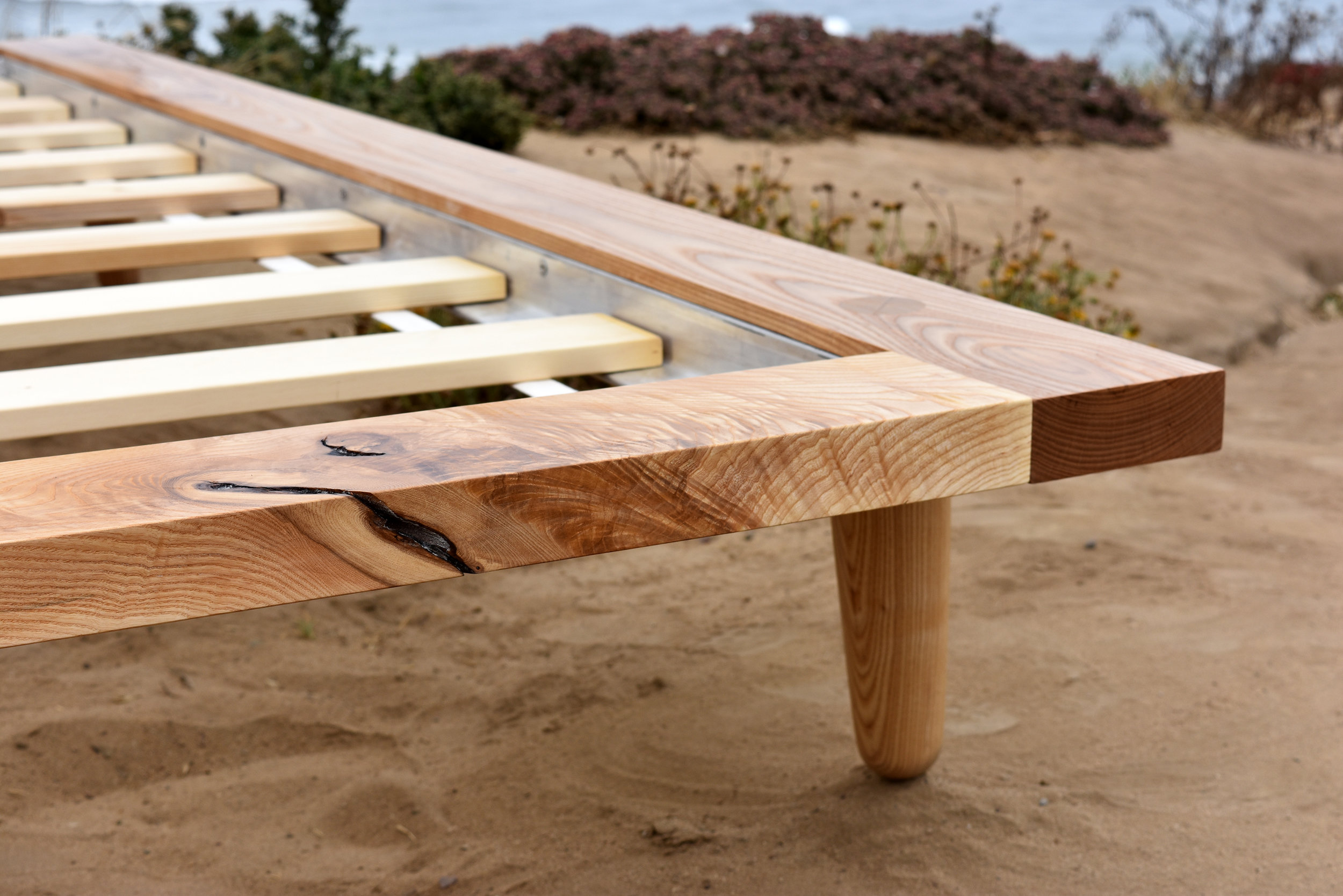Detail view of Coastal bed frame. Solid ash with wedged through tenon legs
