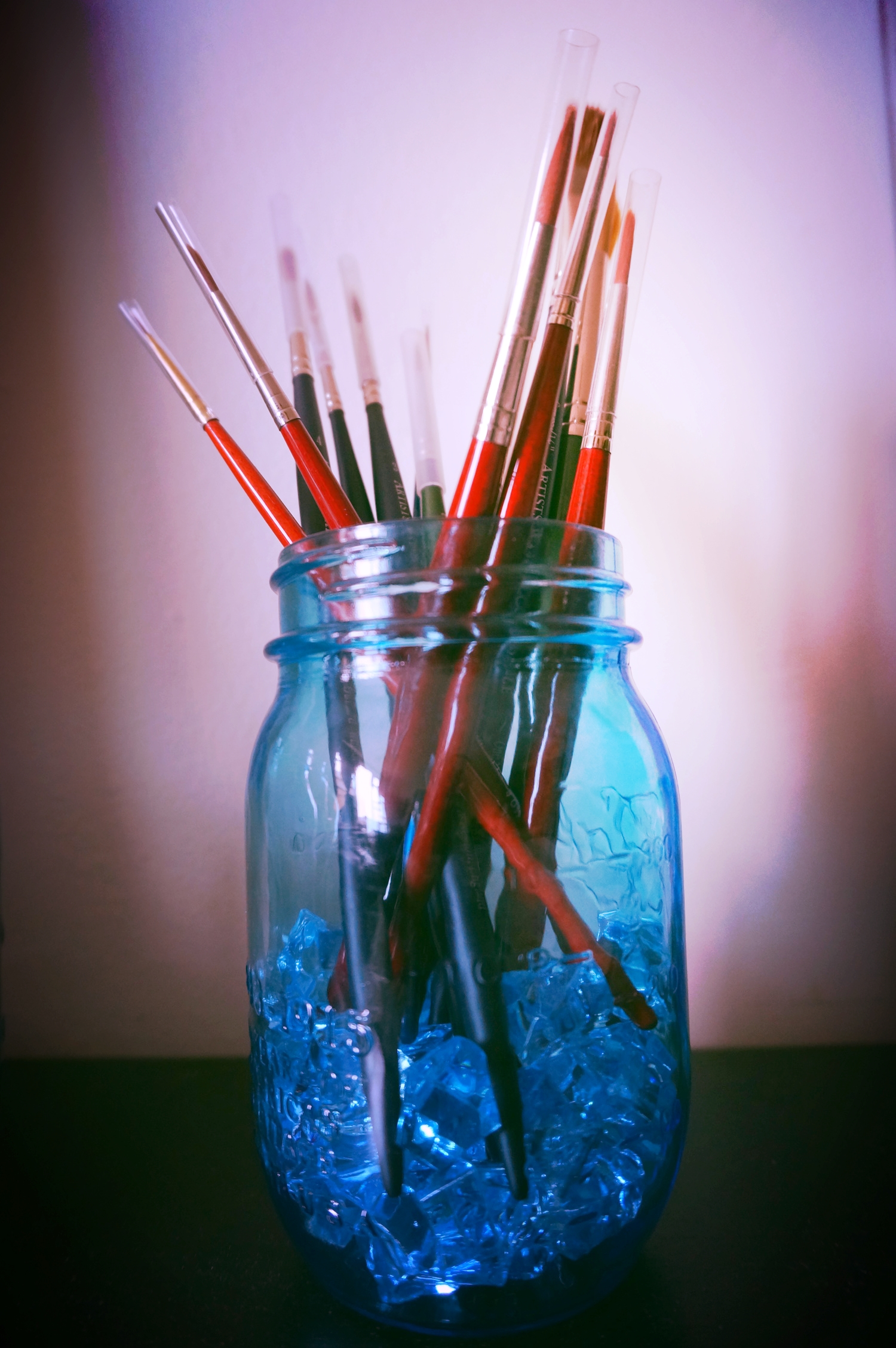I store my brushes upright in a blue tinted mason jar