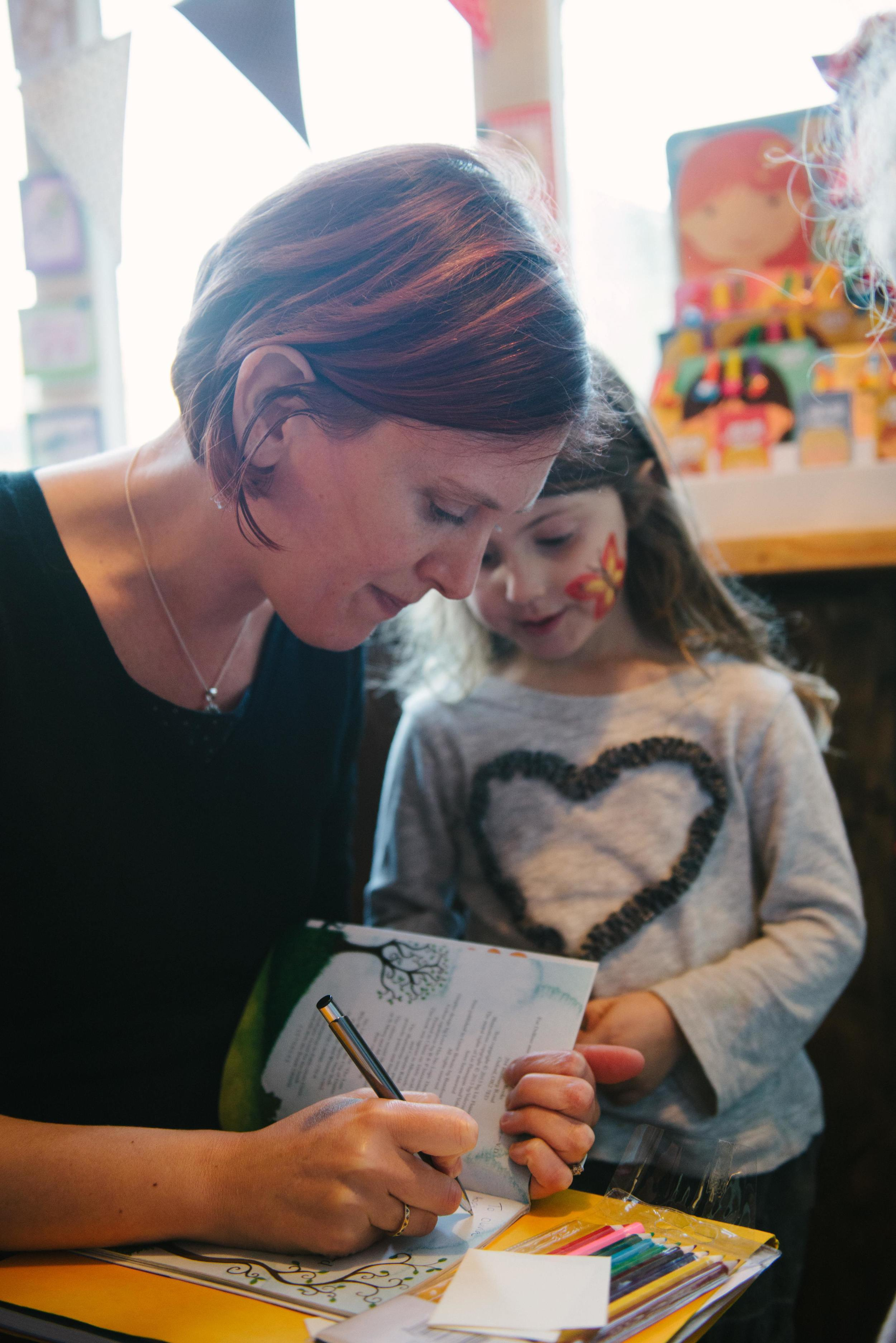 Liz signing books for children, by Sarah Mason Photography