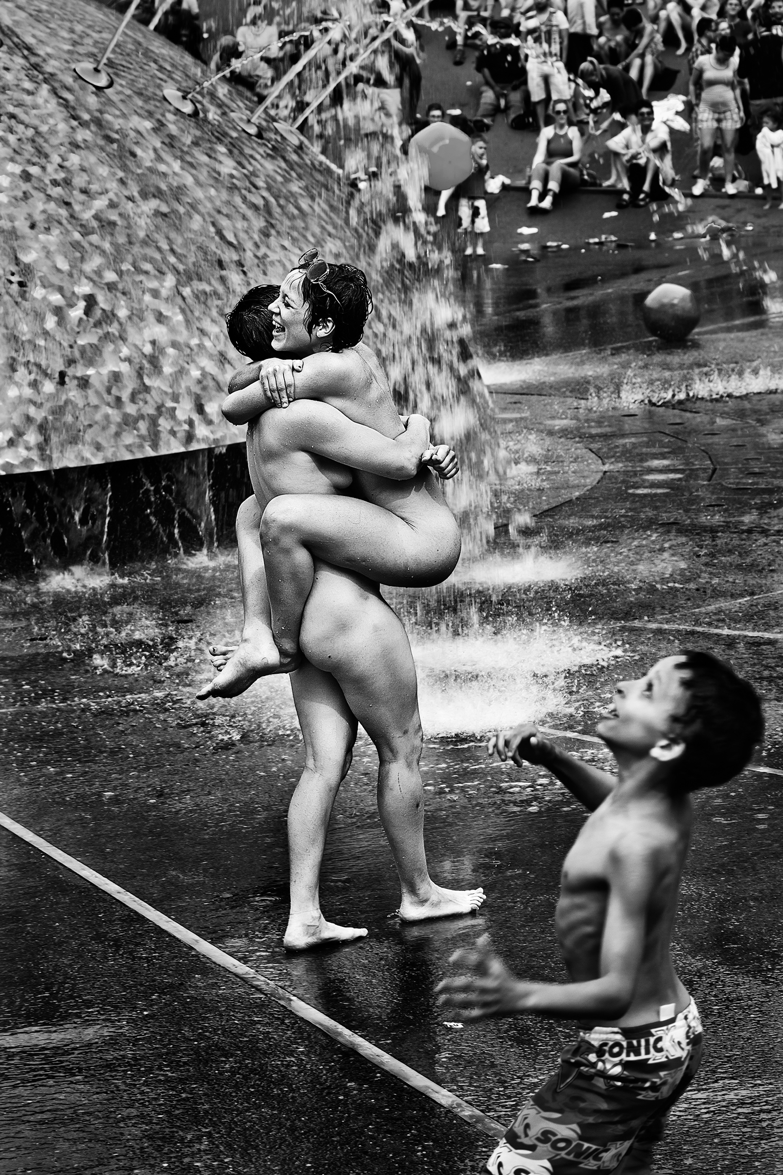 Two women embrace while a boy plays ball at the International Fountain at Seattle PrideFest on June 26th, 2011.