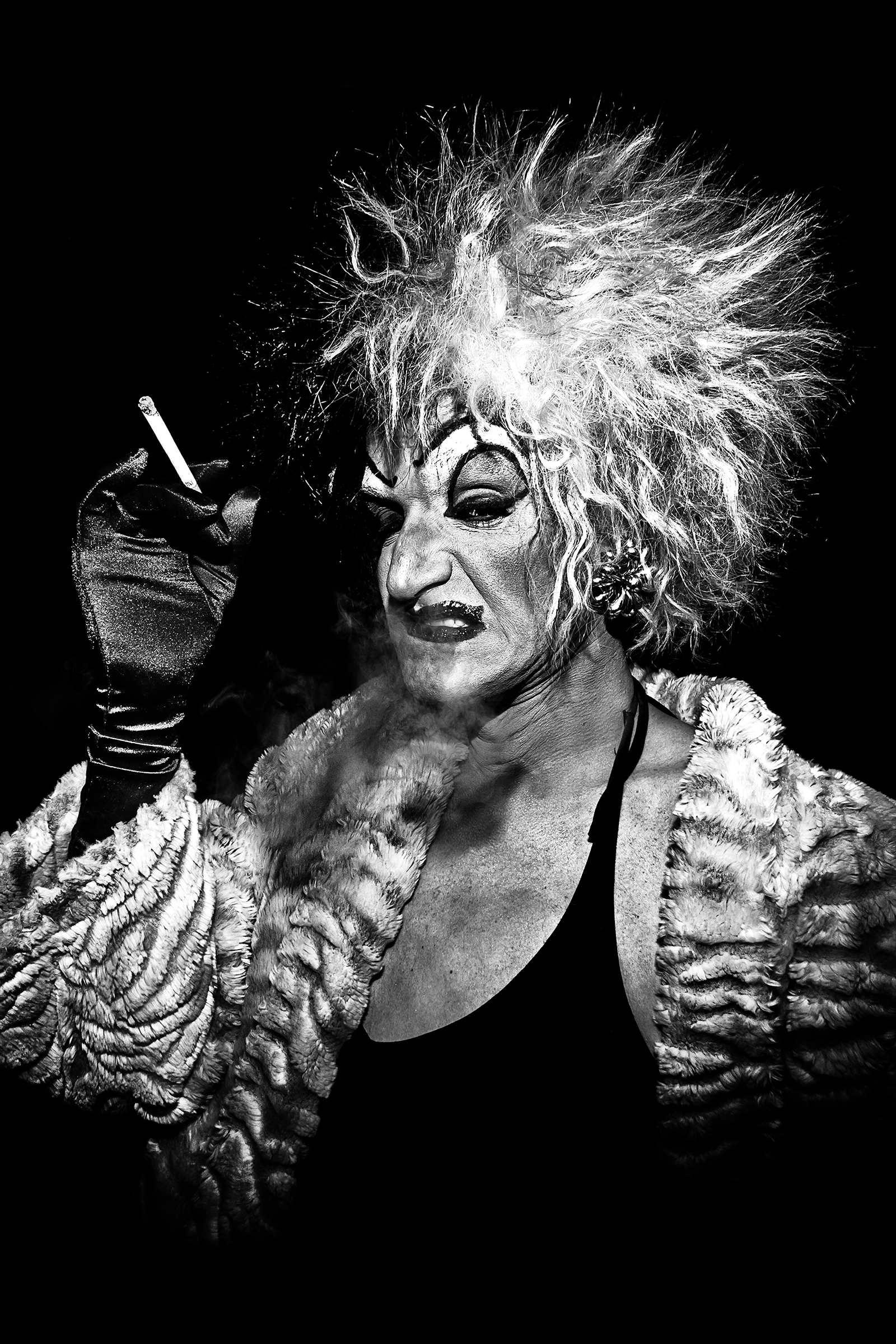 """Local legend Mark """"Mom"""" Finley drags on a cigarette while dressed as Cruella de Vil outside Baltic Room on February 24th, 2012, in Seattle."""