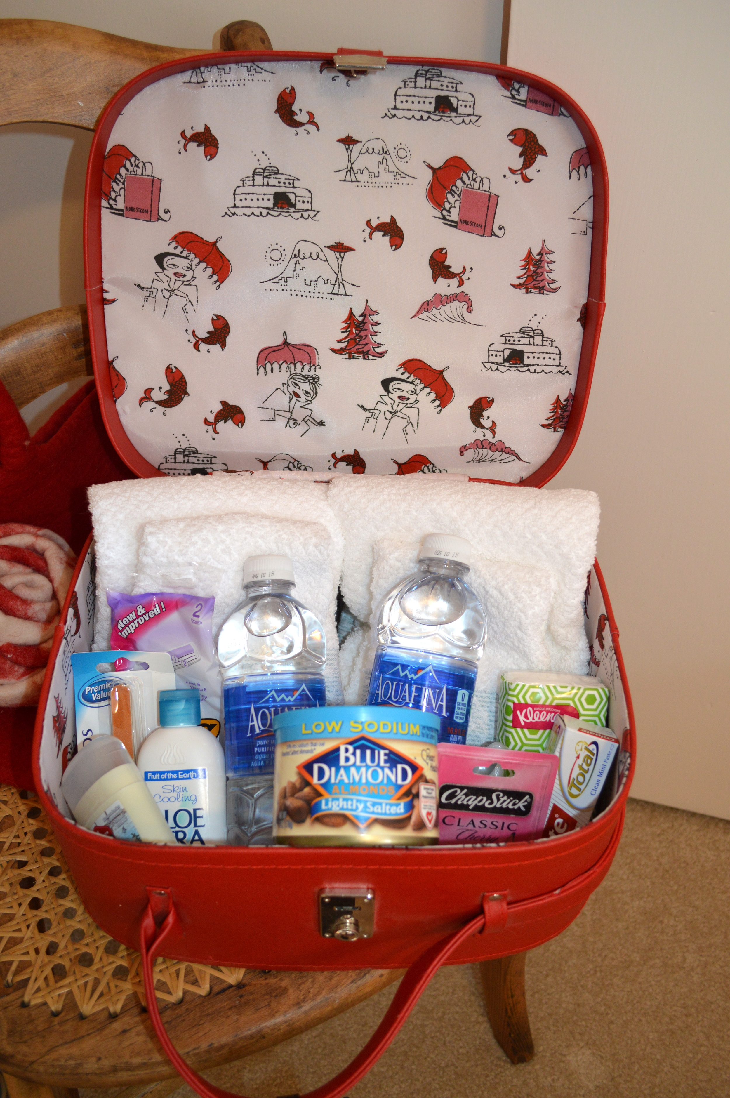 Cosmetic case with guest amenities...water, lotion, nail files, shaver, deodorant, toothpaste and brush, ChapStick, and almonds.