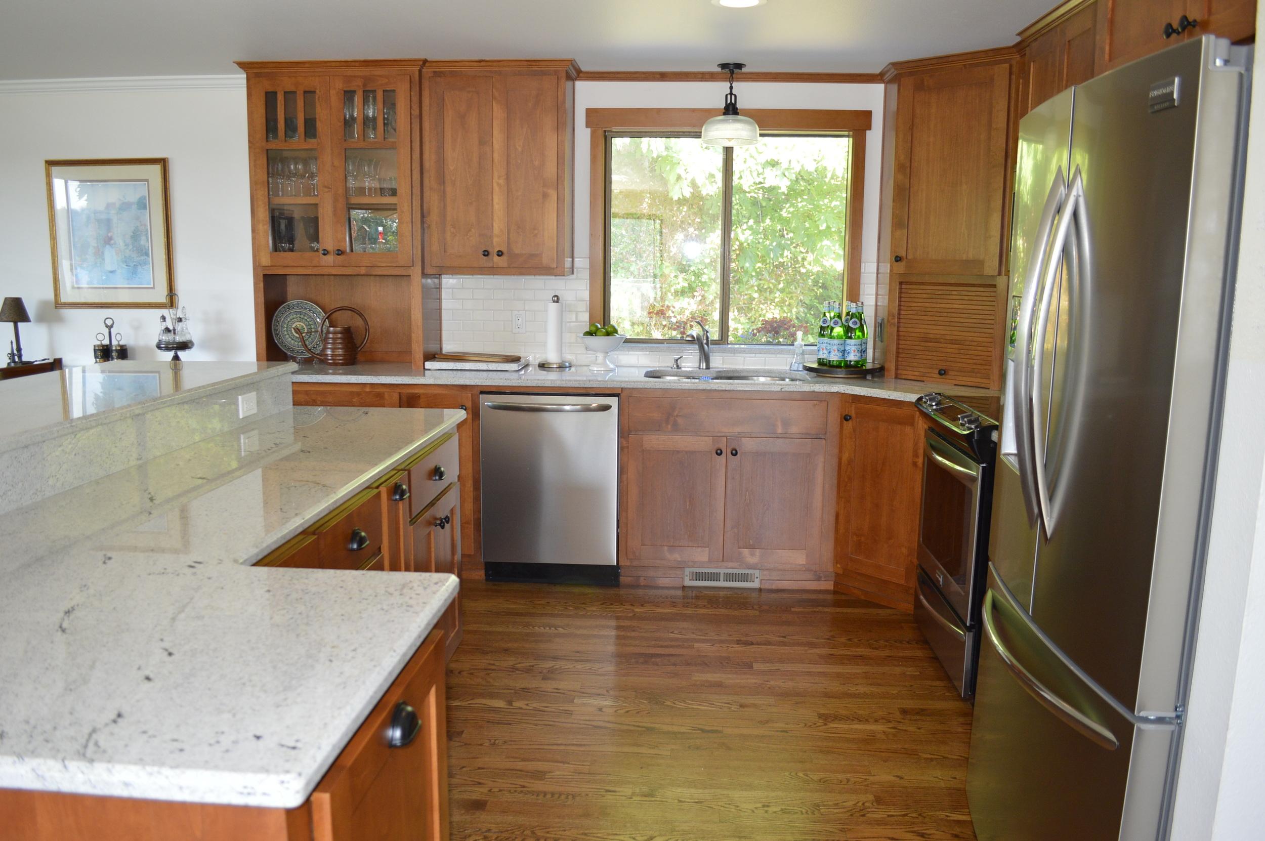 Lovely shaker style Alder cabinets and Nordic White granite...