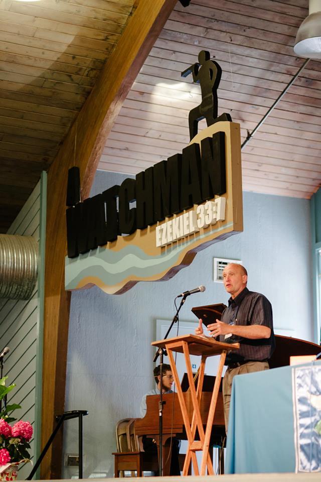 Pastor Mark's artistic banner...(with Pastor Steve Snipstead speaking, photo by Ruth Gunderson).