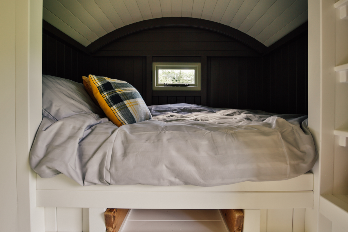 Interior photography of shepherds hut guest room cabin bed