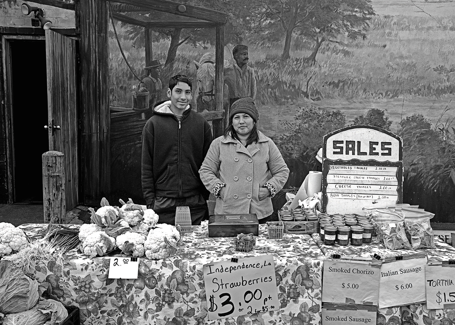 Photographer: David G. Spielman.Maria Mendez and her son at a farmers market selling their produce.