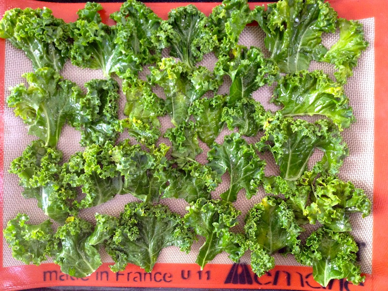 Coat the kale with olive oil, which makes them crispy. Arrange the kale 1 layer deep on a non-stick baking sheet. Sprinkle with salt and pepper. You add chili flakes if you like.