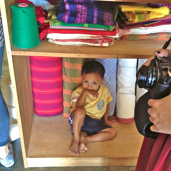 Aling Naty's grandson with finished textiles at the weaving center.
