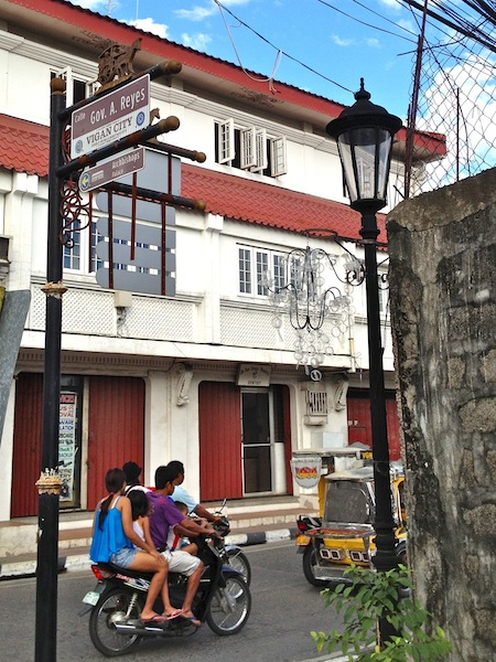 I meant to take a photo only of the street sign detail. I love the vintage  kalesa that's part of the sign post! Then I couldn't resist including the family of 4 on a scooter.