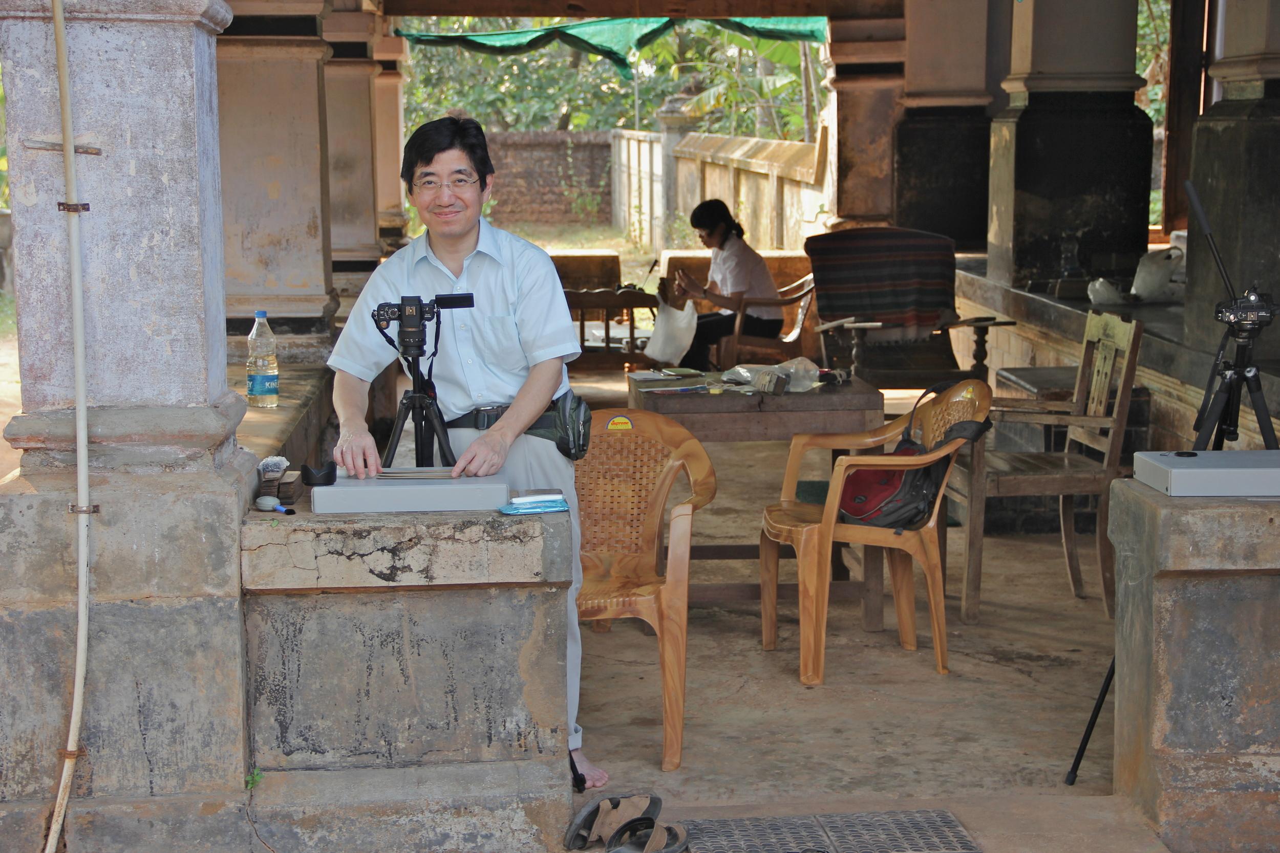 Masato Fujii (with Mieko Kajihara in back) photographing manuscripts near Irinjalakuda, Kerala.