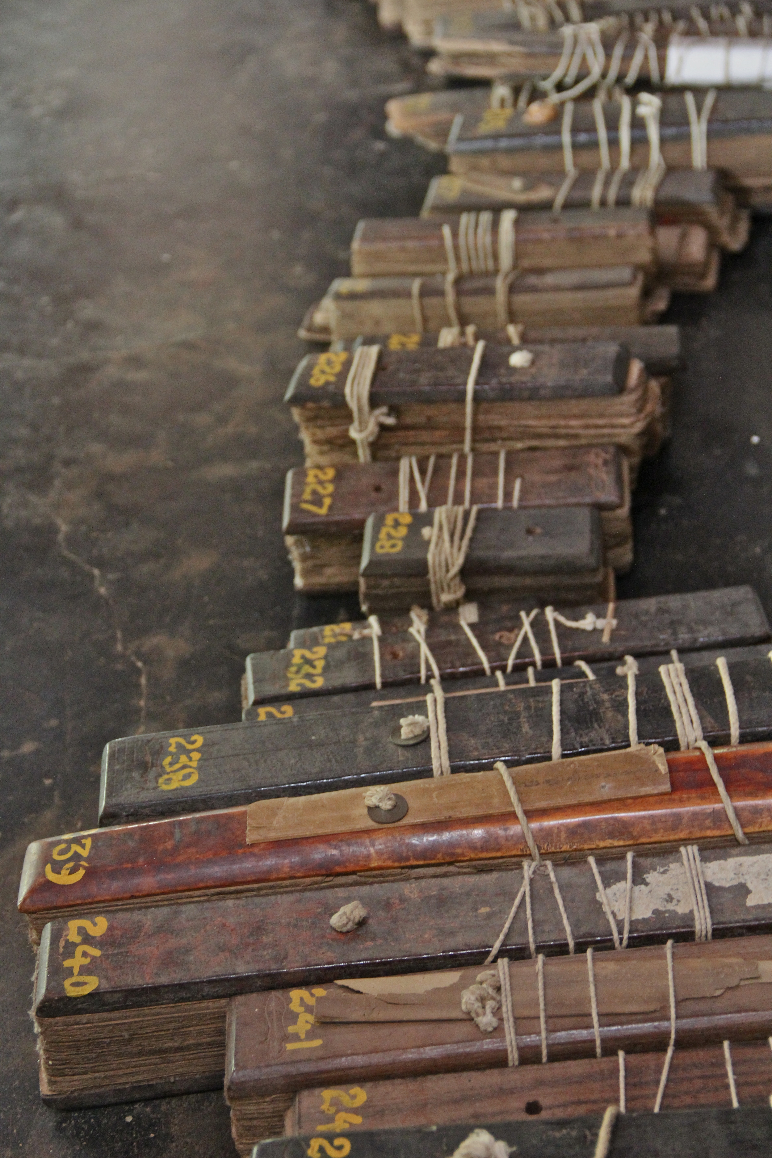 """A small portion of a Kerala manuscript collection: stacks of palm-leaves, incised with text on both sides and stacked like cards, are clamped between wooden covers and tied with string threaded through holes in the middle. Each """"book"""" has been numbered in yellow by modern researchers..."""