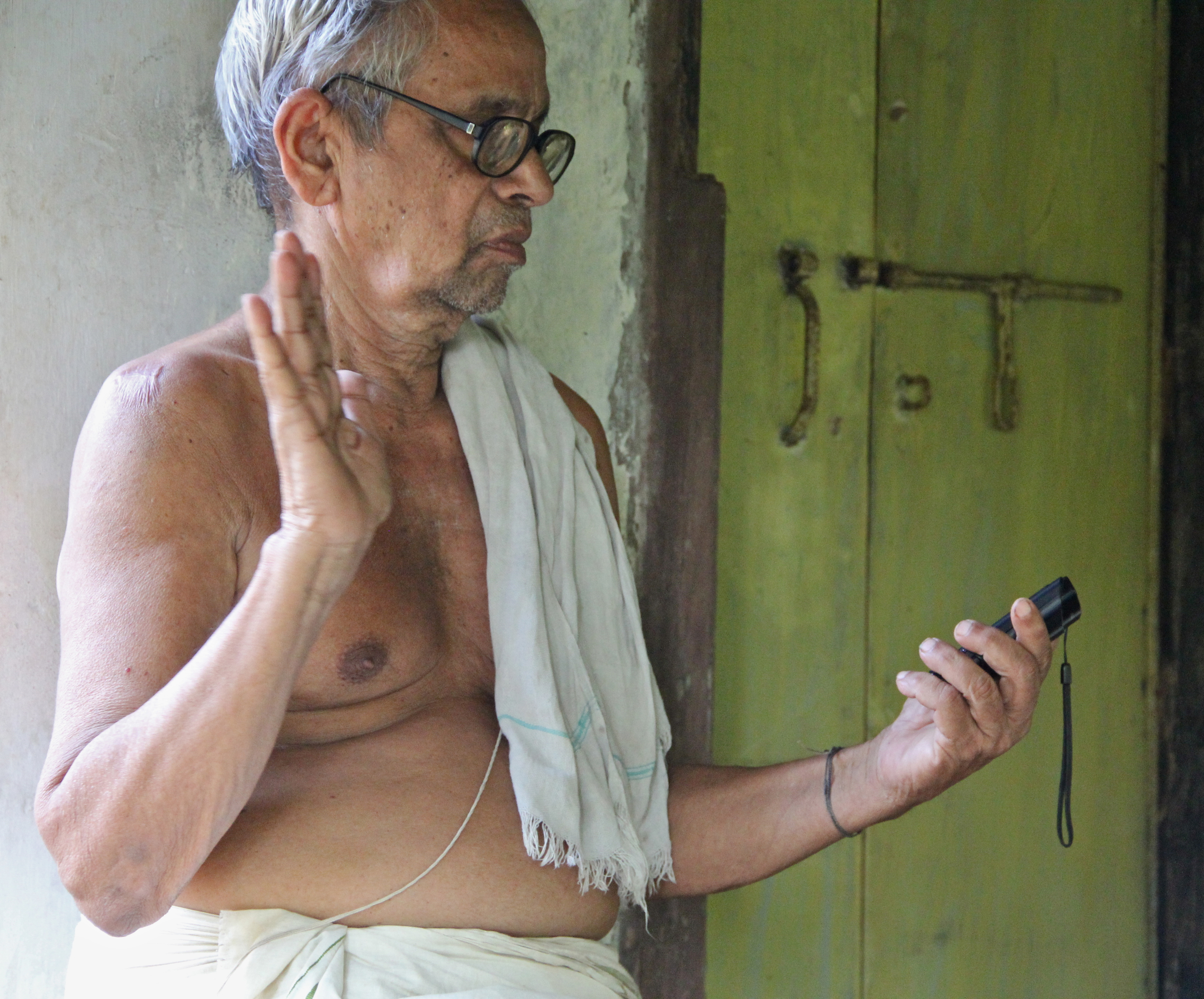 §1.1, 1.3 Vasudevan consulting a portable media player with audio of his own recorded performance, exemplifying the Jaiminīya  digital agency