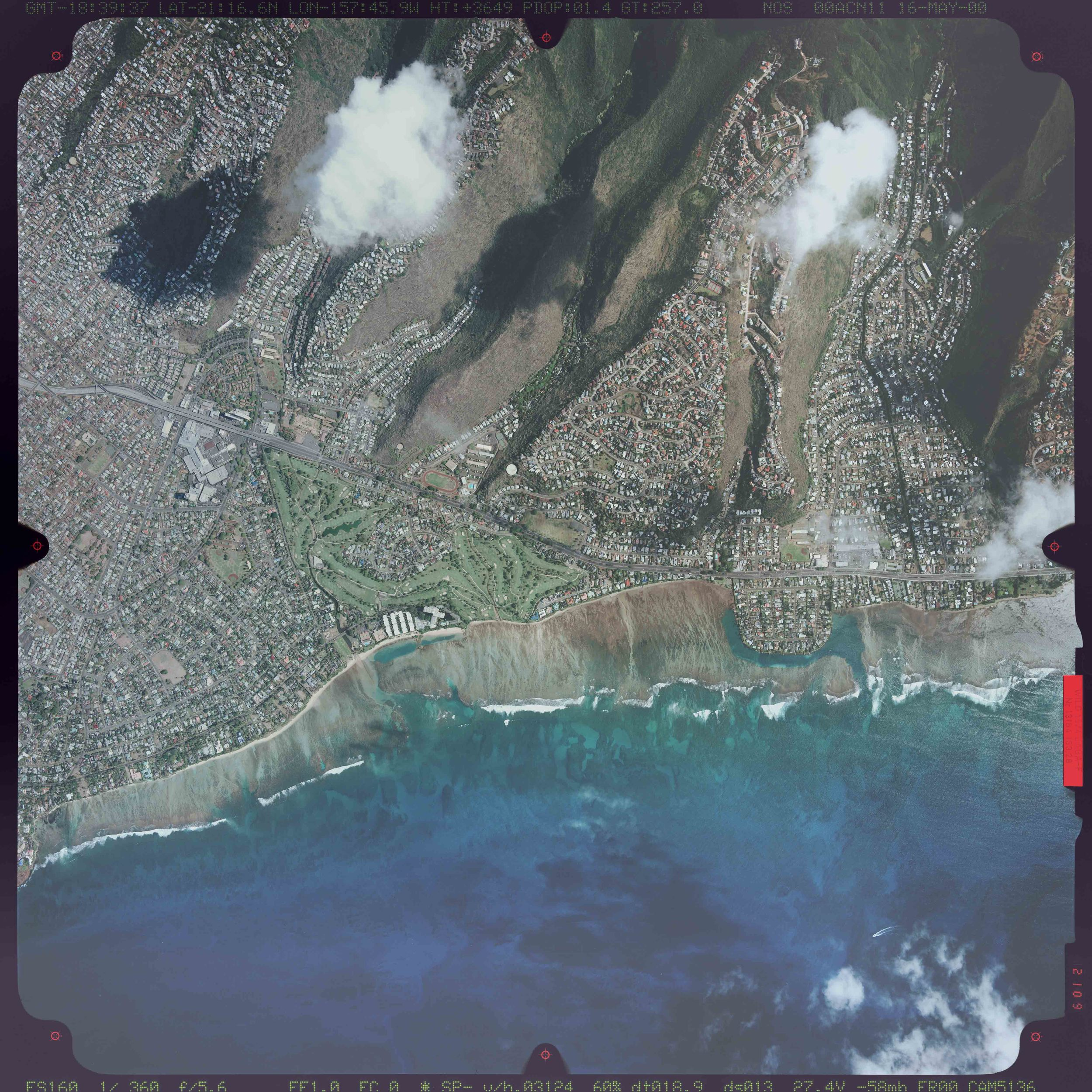 """The Ko'olau Range intermingles with neighborhoods of Honolulu.  [Image:National Oceanic and Atmospheric Administration. """"Frame: 2109"""" [aerial photograph]. Scale ~1in:1km. Flight line No: 018. 16/5/00.  Downloaded from    http://magis.manoa.hawaii.edu/viewer/   on 15/2/14. ]"""