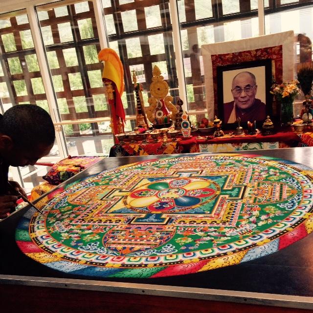 Tibetan monks put the finishing touch on a sand mandala at the Aspen Art Museum.