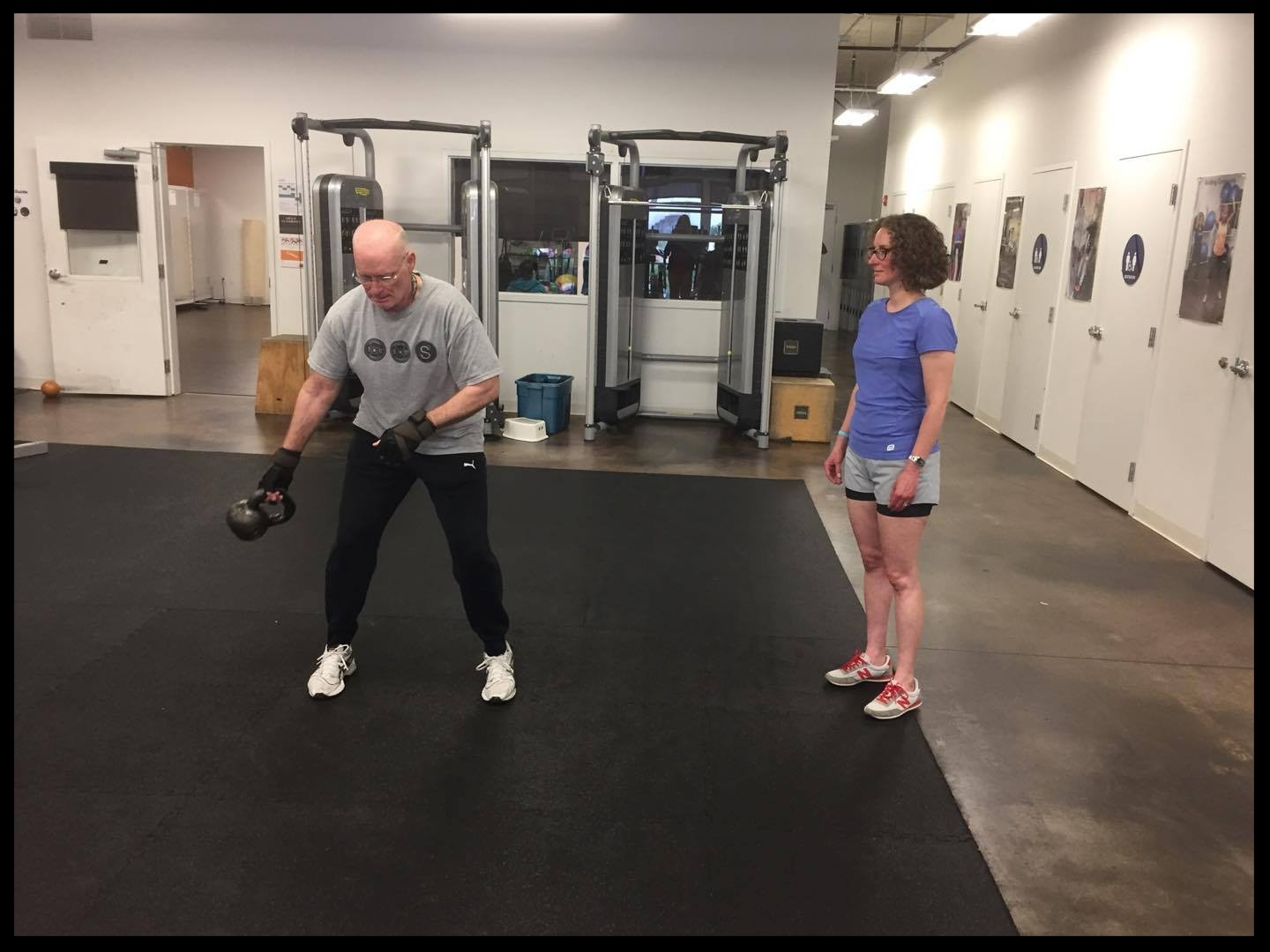 Leo swings a kettle bell while Rachel waits for her turn