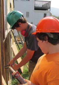 TTC Students repair wood shop wall.
