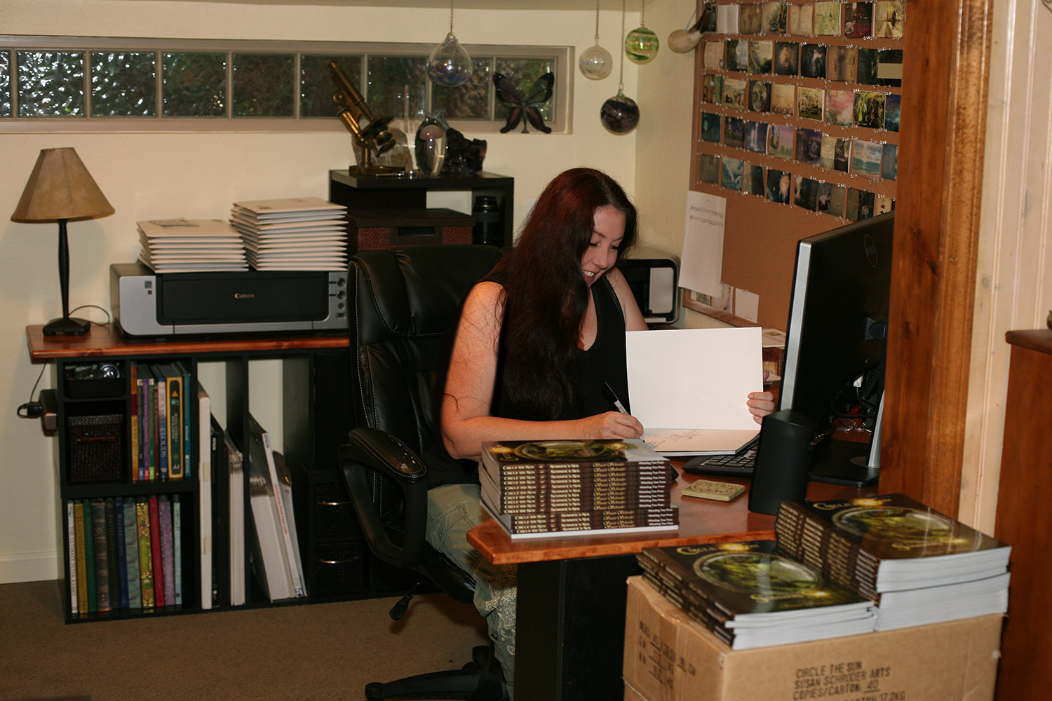 Susan happily signing and shipping books!