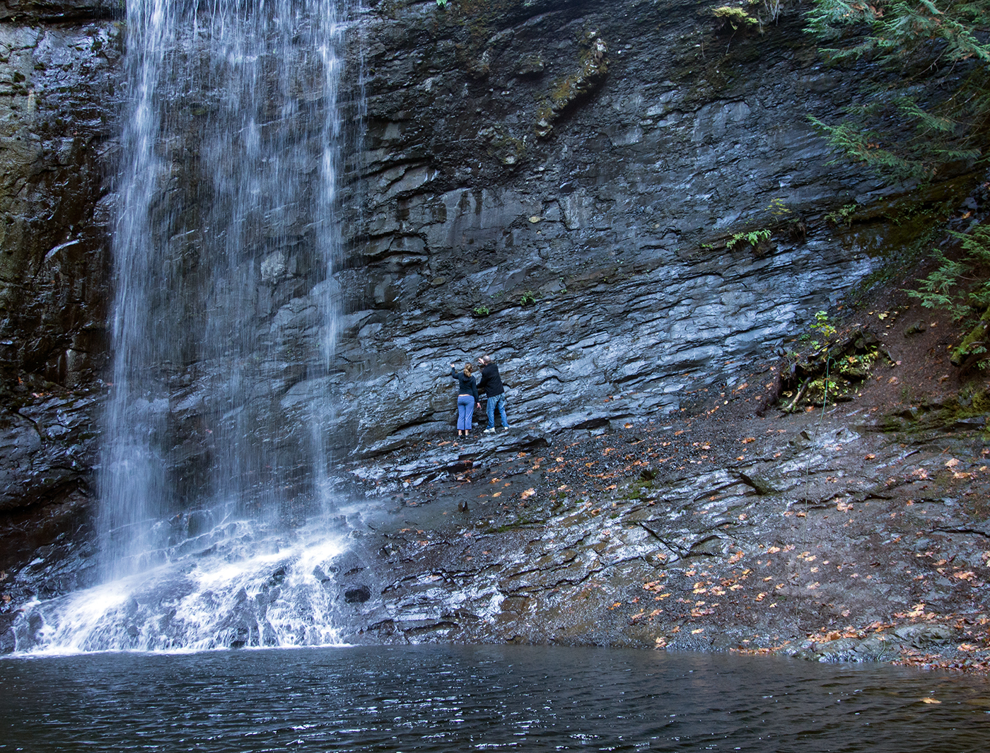 Two hikers explore the base of Ammonite Falls for fossils