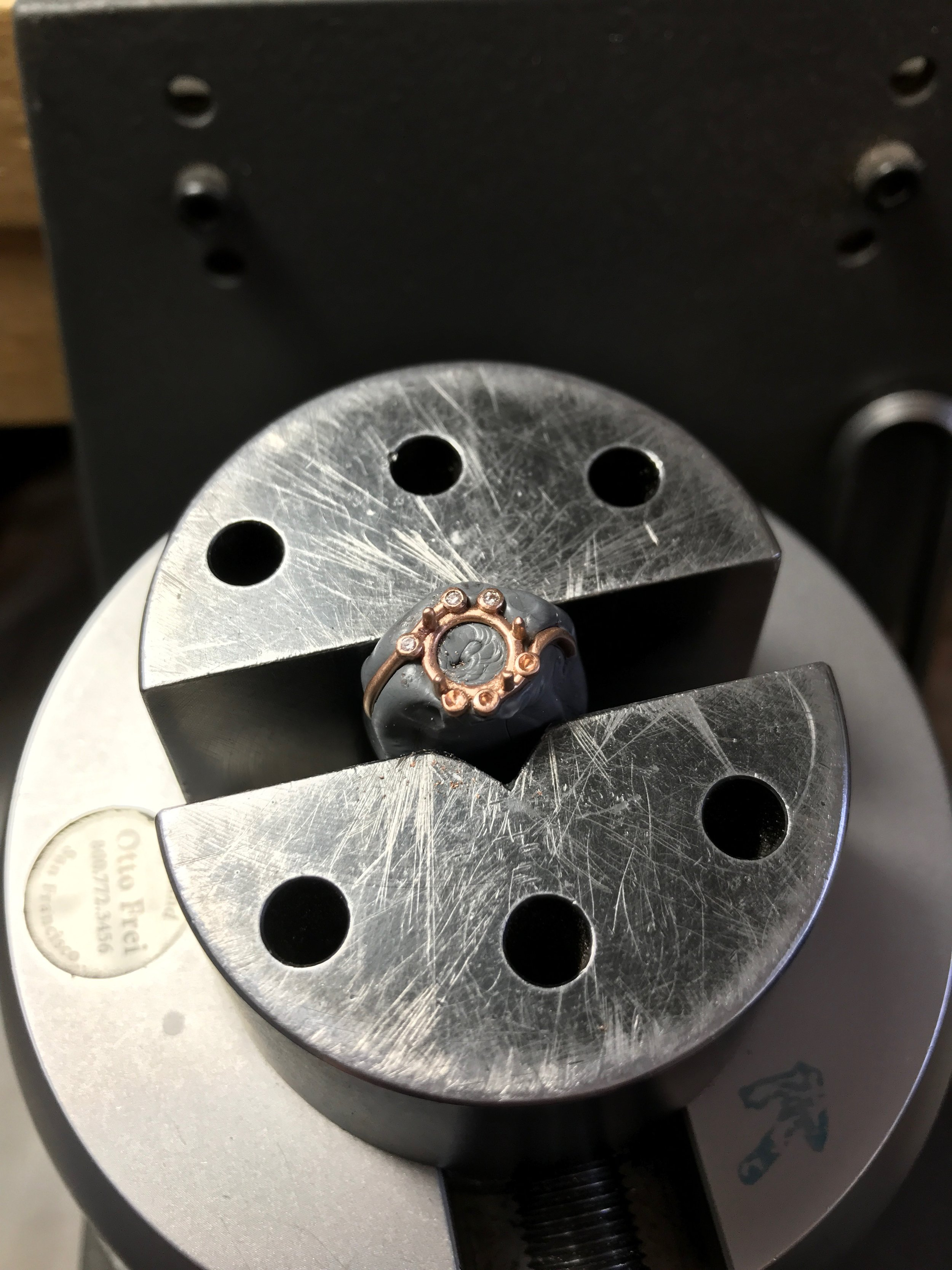 process - Setting the diamonds. The piece is held in thermoplastic and then clamped in an engraver's block.