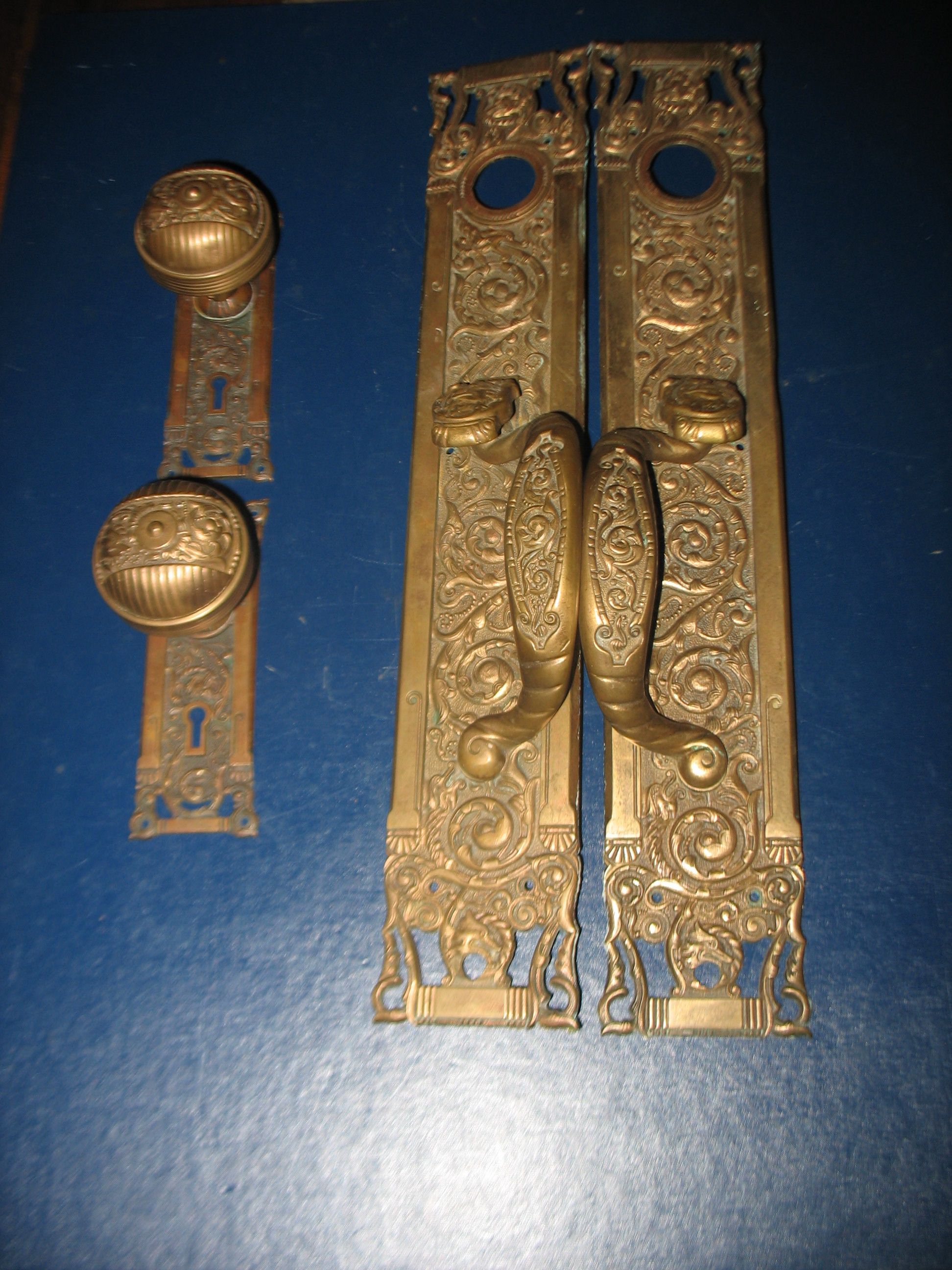 "This bronze Entry Door Set is authentic antique door hardware at its very best! The Reading Hardware Company created this gorgeous pattern in the late l800's. It  is the ""Columbian""pattern cast in bronze and caleed. The set consists of two thumb paddle door pulls measuring 18 1/2 inches long X 3 1/4 inches wide. There are two escutcheons, 6 inches long X 2 inches wide, and 2 door knobs  all with the famous wolf/fox heads on each piece, beautifully detailed and heavily cast."