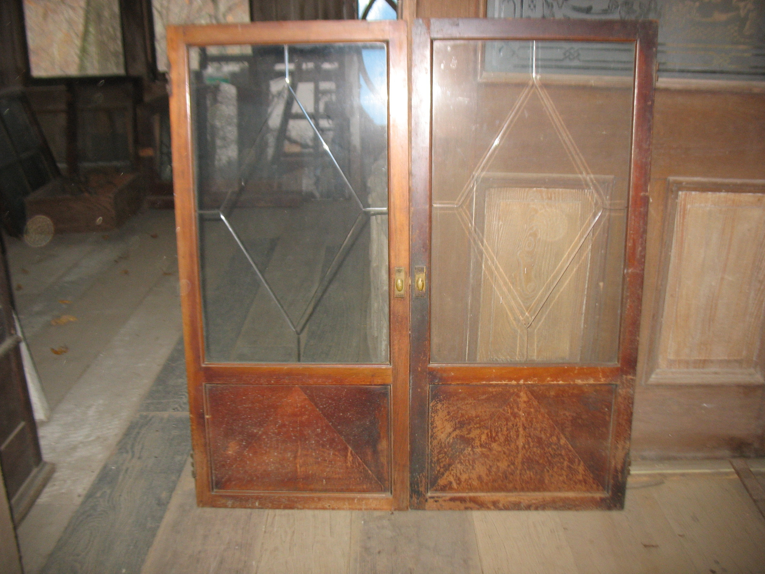 This is a very unusual pair of cabinet doors from a wonderful library in a house in New Orleans. Would make any cabinet beautiful. The heavy glass is hand cut in a diamond design and framed in walnut with original hardware. They measure 49 inches tall X 44 inches overall width. Each window being 22 1/2 inches wide.
