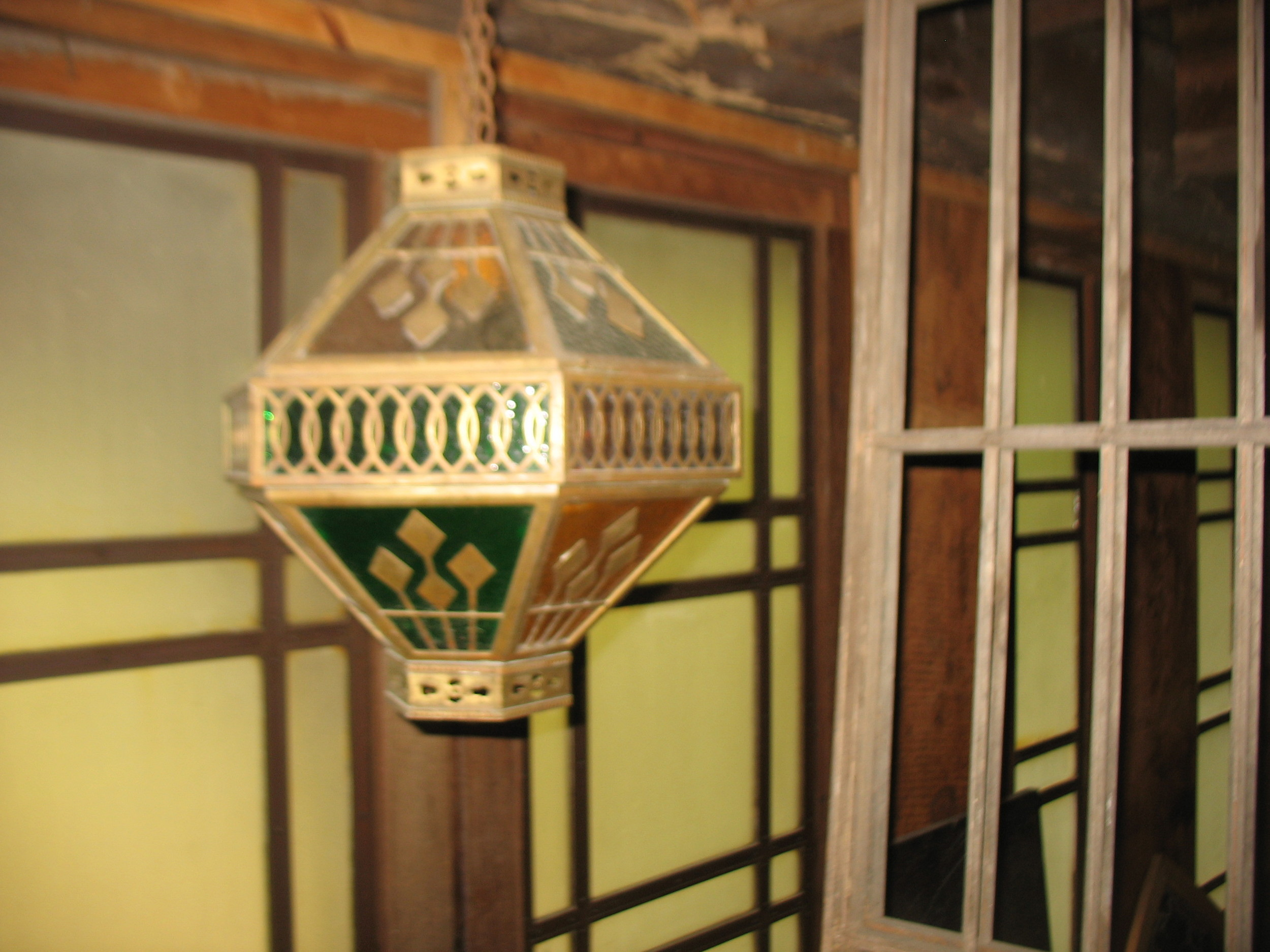 This is a charming little light. It has cut brass decorative pieces which are over colored glass which is in green and amber. Its hang on a brass chain one can lengthen any way they need for the right length