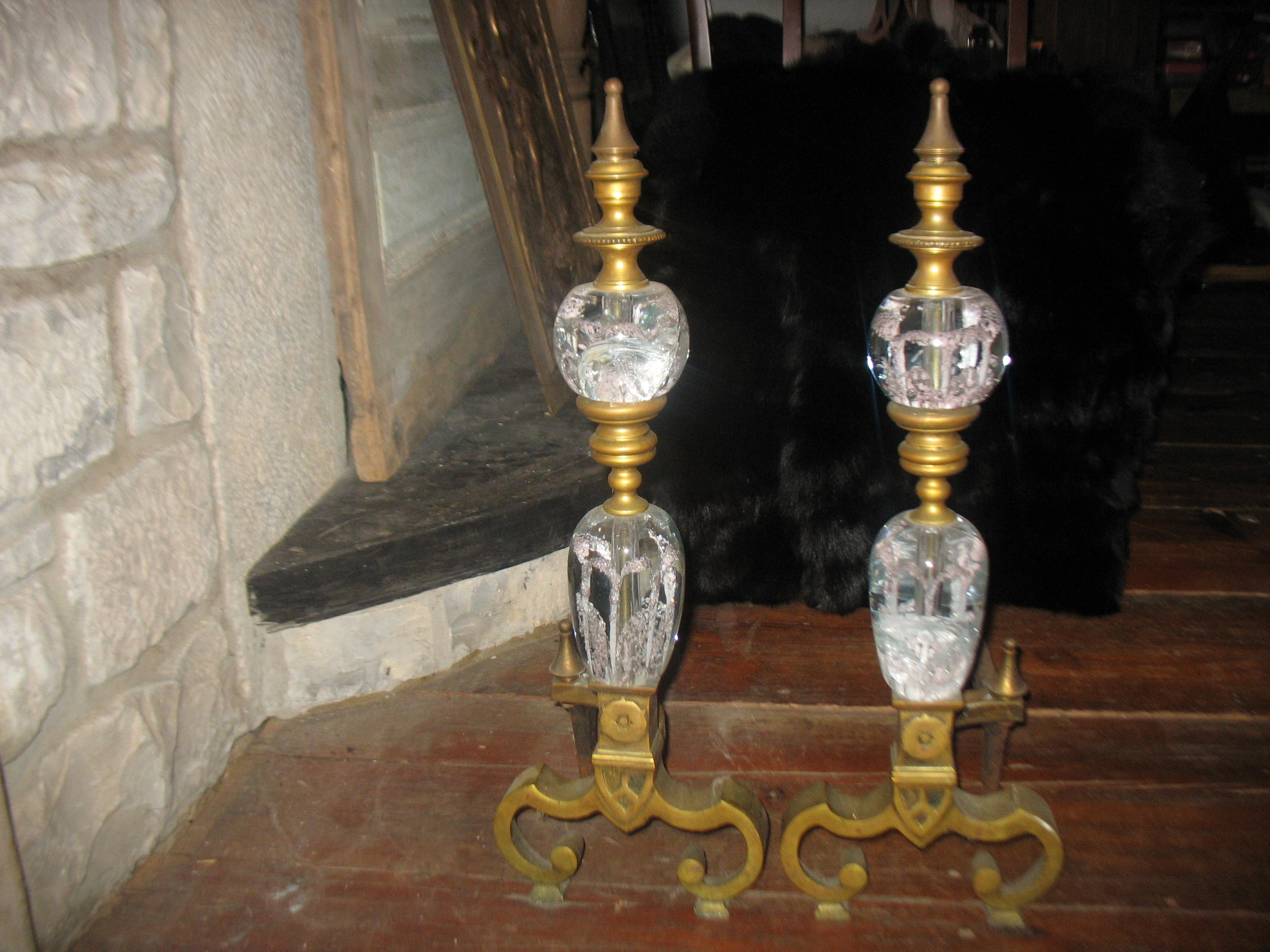 Beautiful pair French Brass/Glass Chenets. This is a very elegant pair for a small fireplace in a ladies boudoir. The glass is blown with pink flowers blown inside the glass. The base is a curved gracefully fashioned brass with brass separating each piece of glass and finished with brass finials on top. There are two cracked places unfortunately in one of the bottom glass pieces and one of the top, but still a work of art. Therefore I am asking only a fraction of what they are worth. These would be exclusively for a decorative effect in the fireplace.