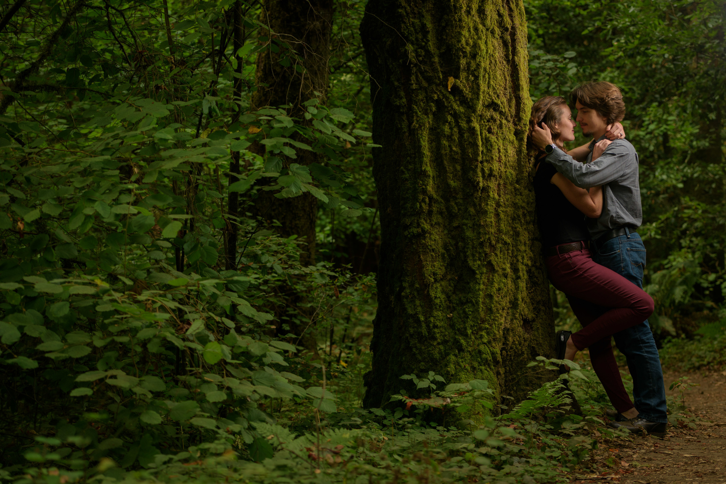 Girl leaned up against a redwood tree with fiance facing her - Engagement Photos in Nisene Marks Forest in Aptos, CA - by Bay Area wedding photographer Chris Schmauch