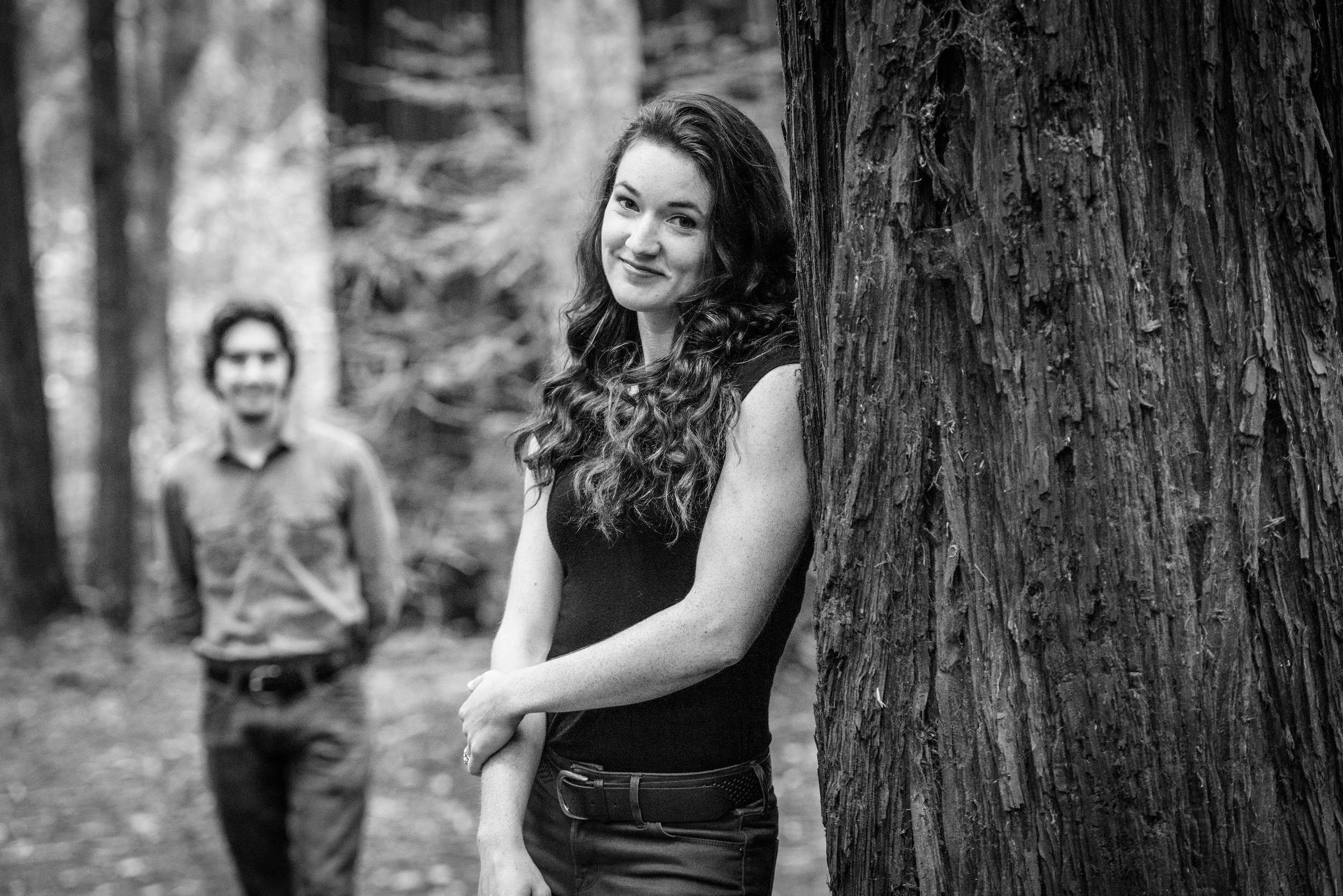 Girl leaning against tree looking at camera with fiance in background - Engagement Photos in Nisene Marks Forest in Aptos, CA - by Bay Area wedding photographer Chris Schmauch
