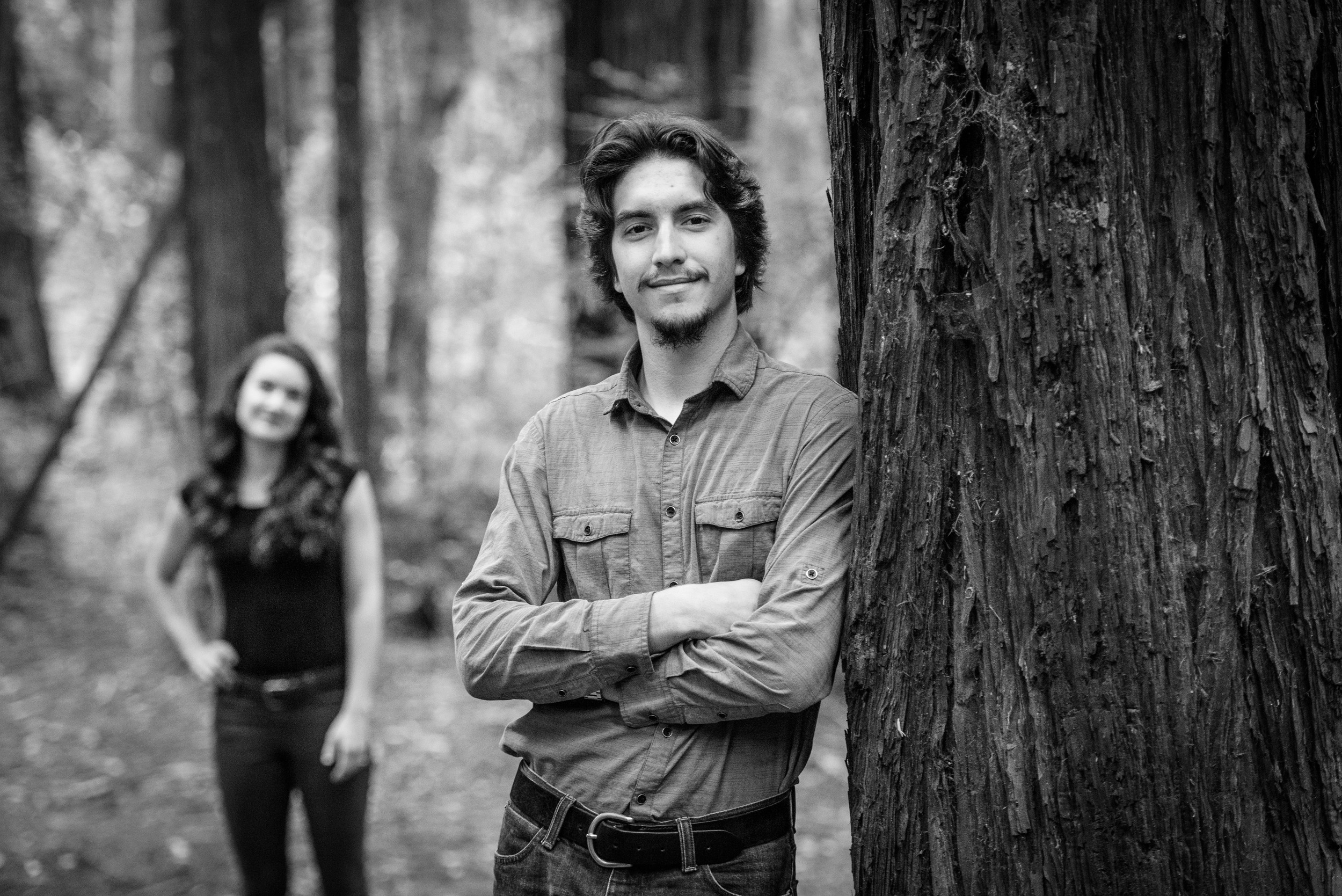 Man leaning against redwood tree looking at camera with fiancee in the background - Engagement Photos in Nisene Marks Forest in Aptos, CA - by Bay Area wedding photographer Chris Schmauch