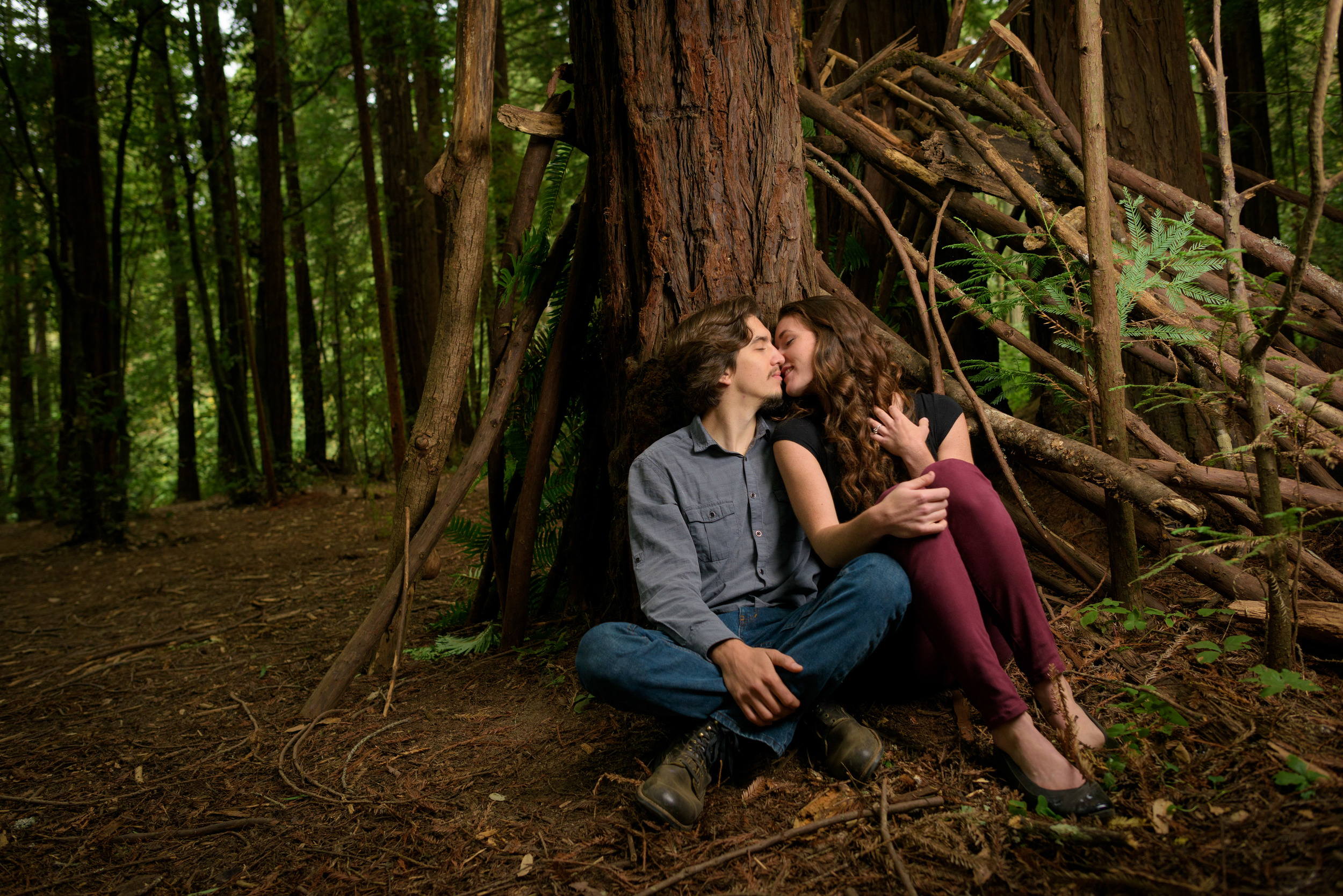 Couple kissing while sitting against tree and makeshift tent - Engagement Photos in Nisene Marks Forest in Aptos, CA - by Bay Area wedding photographer Chris Schmauch
