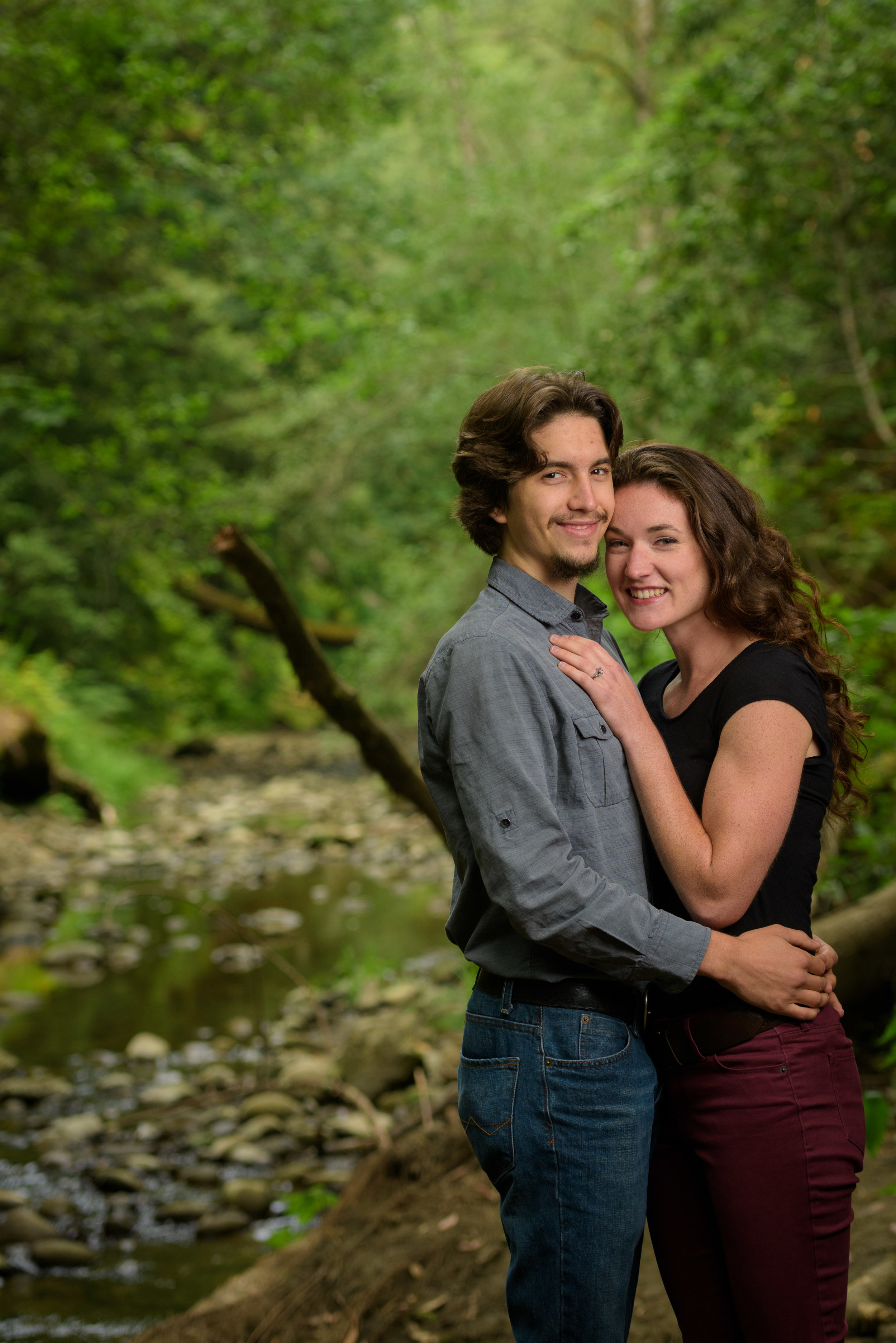 Couple cuddling and looking at camera with creek and forest in background - Engagement Photos in Nisene Marks Forest in Aptos, CA - by Bay Area wedding photographer Chris Schmauch