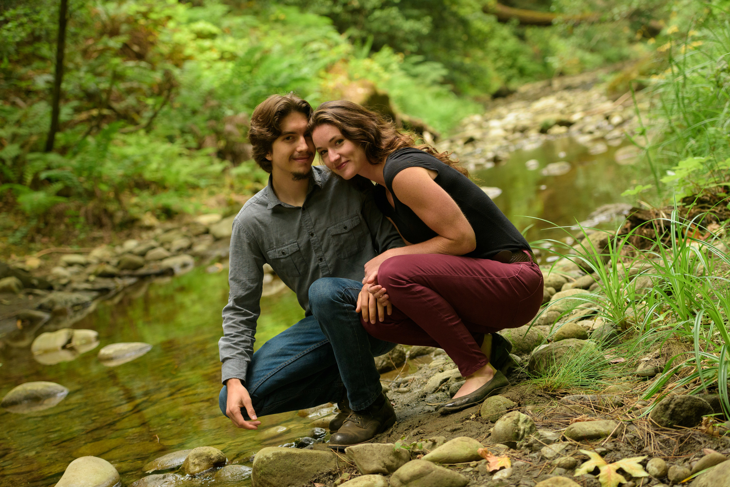 Couple crouching next to creek - Engagement Photos in Nisene Marks Forest in Aptos, CA - by Bay Area wedding photographer Chris Schmauch