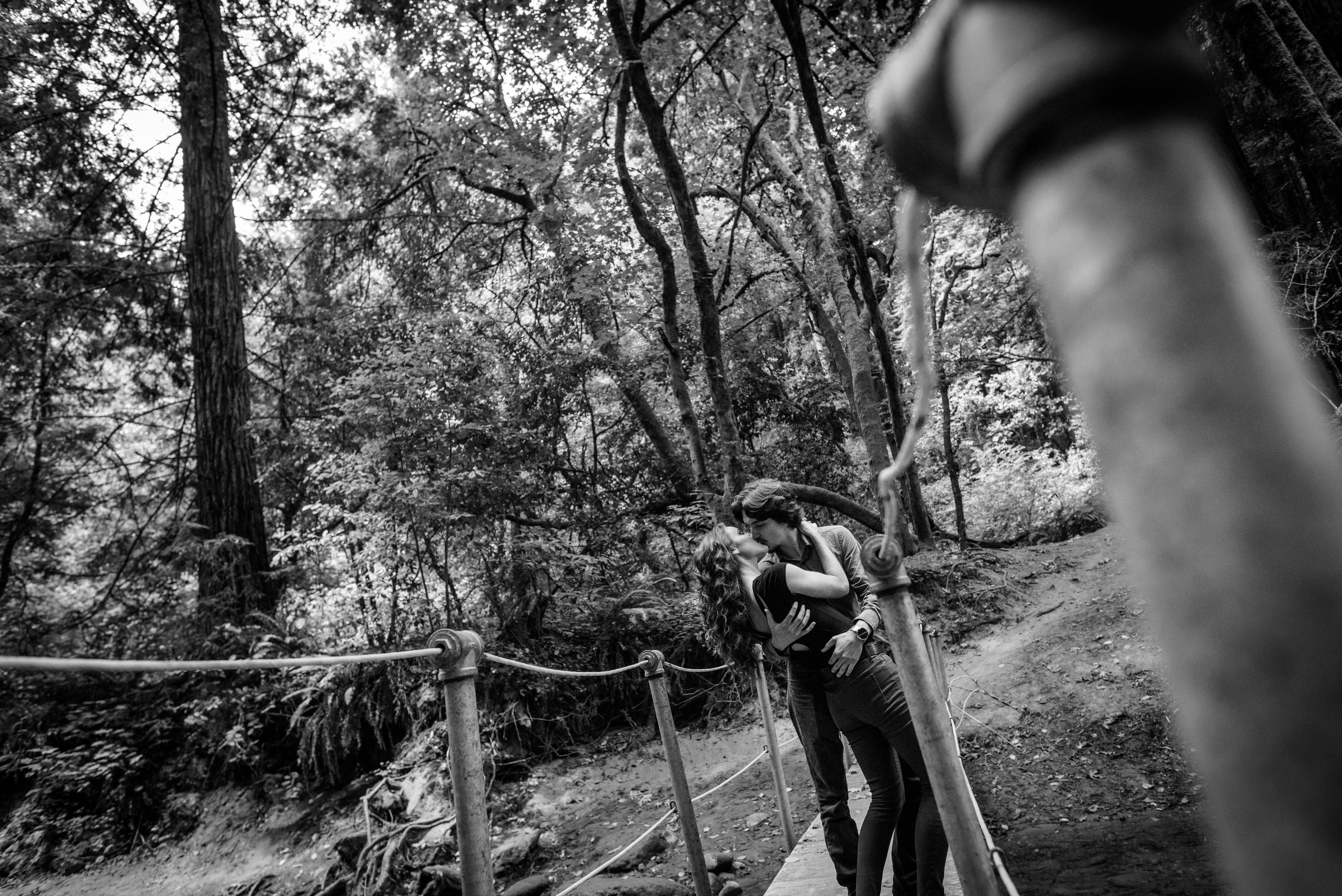 Wide angle B&W couple dipping and kissing on forest creek bridge - Engagement Photos in Nisene Marks Forest in Aptos, CA - by Bay Area wedding photographer Chris Schmauch