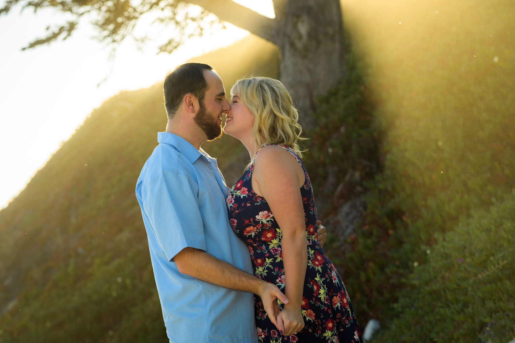 couple kissing with backlit shafts of sunlight - Stewart's Cove - Carmel Engagement Photography - photos by Bay Area wedding photographer Chris Schmauch