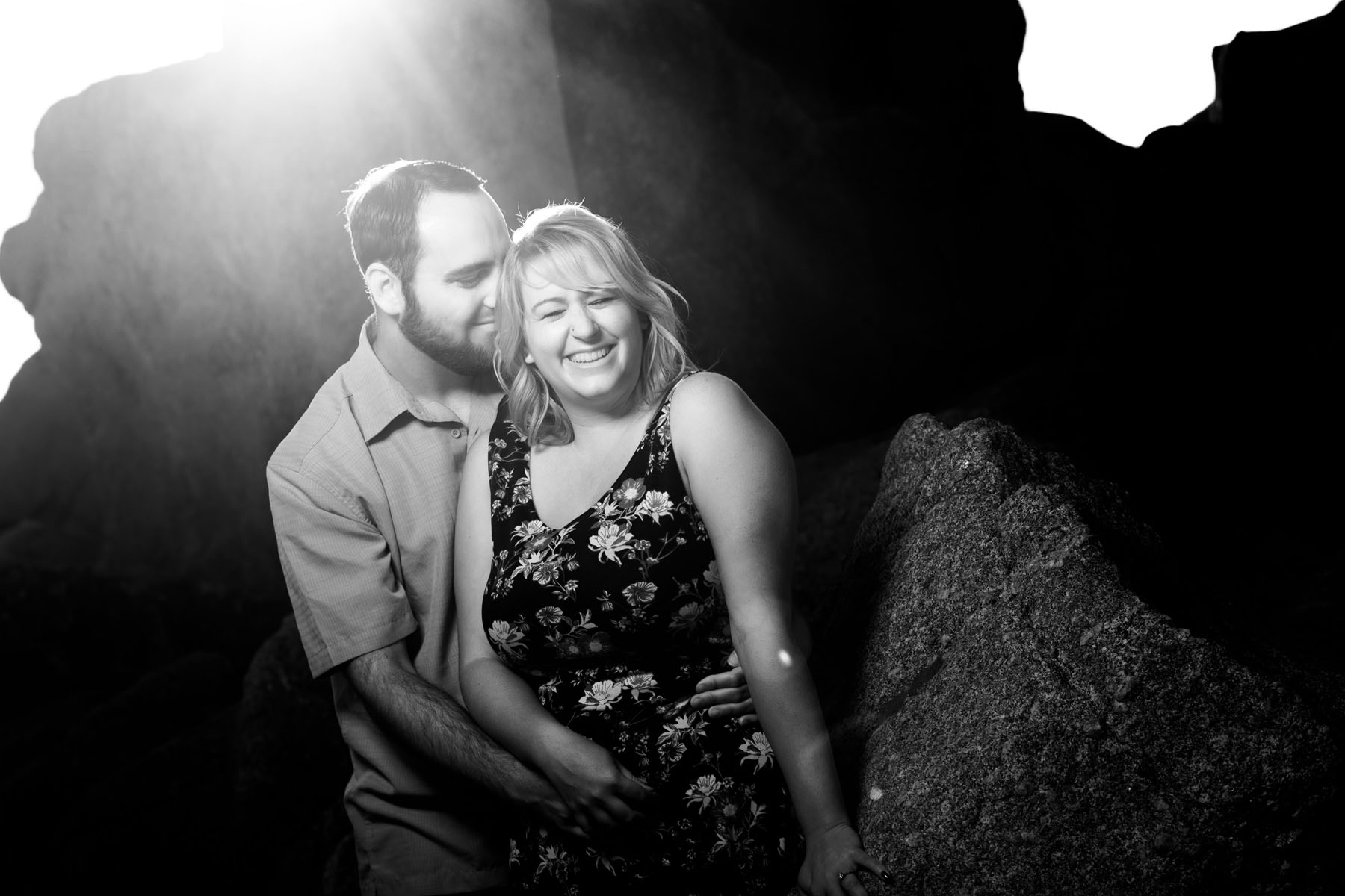 couple cuddling b&w sun flare - Stewart's Cove - Carmel Engagement Photography - photos by Bay Area wedding photographer Chris Schmauch