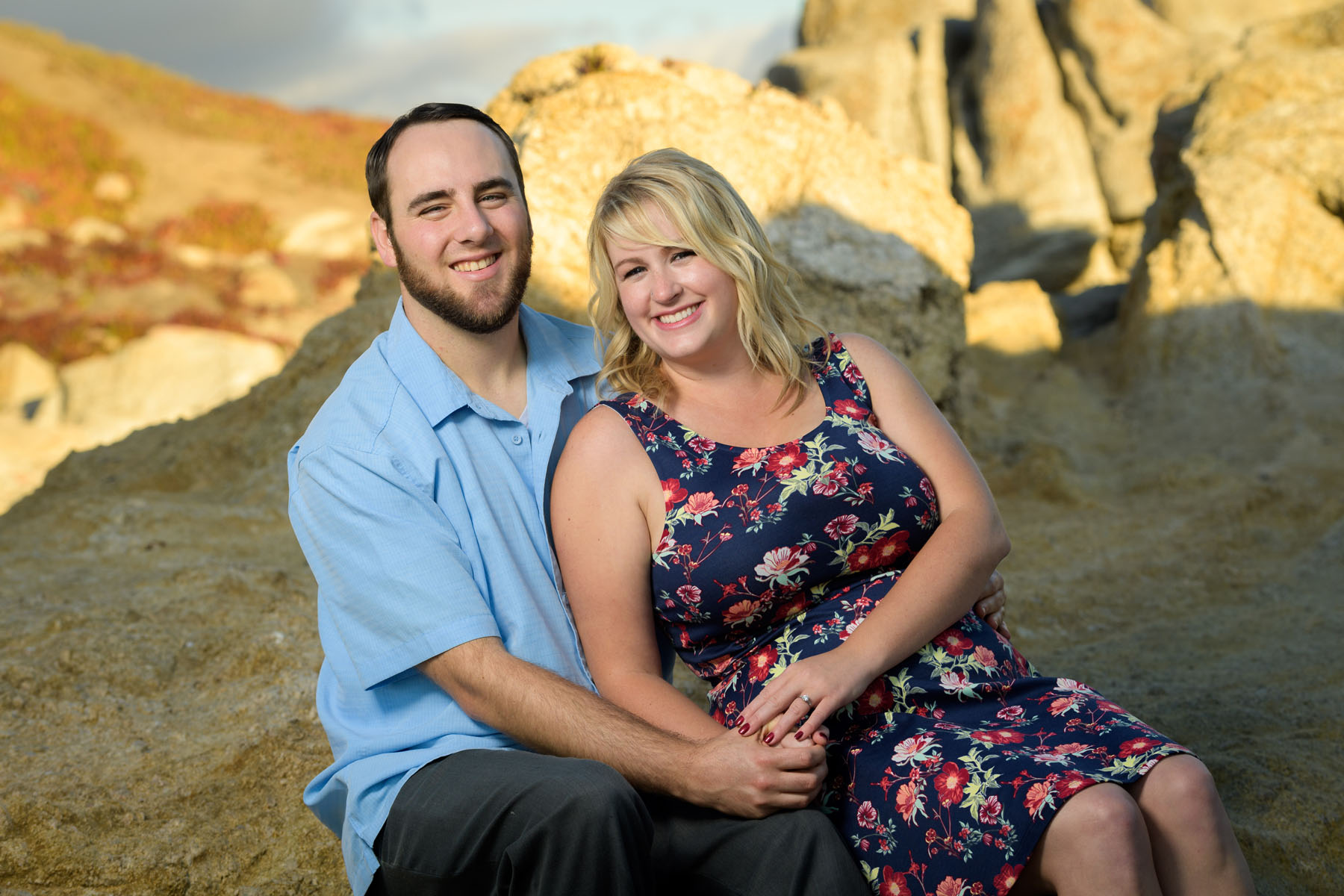 cuddling couple on the beach rock - Stewart's Cove - Carmel Engagement Photography - photos by Bay Area wedding photographer Chris Schmauch