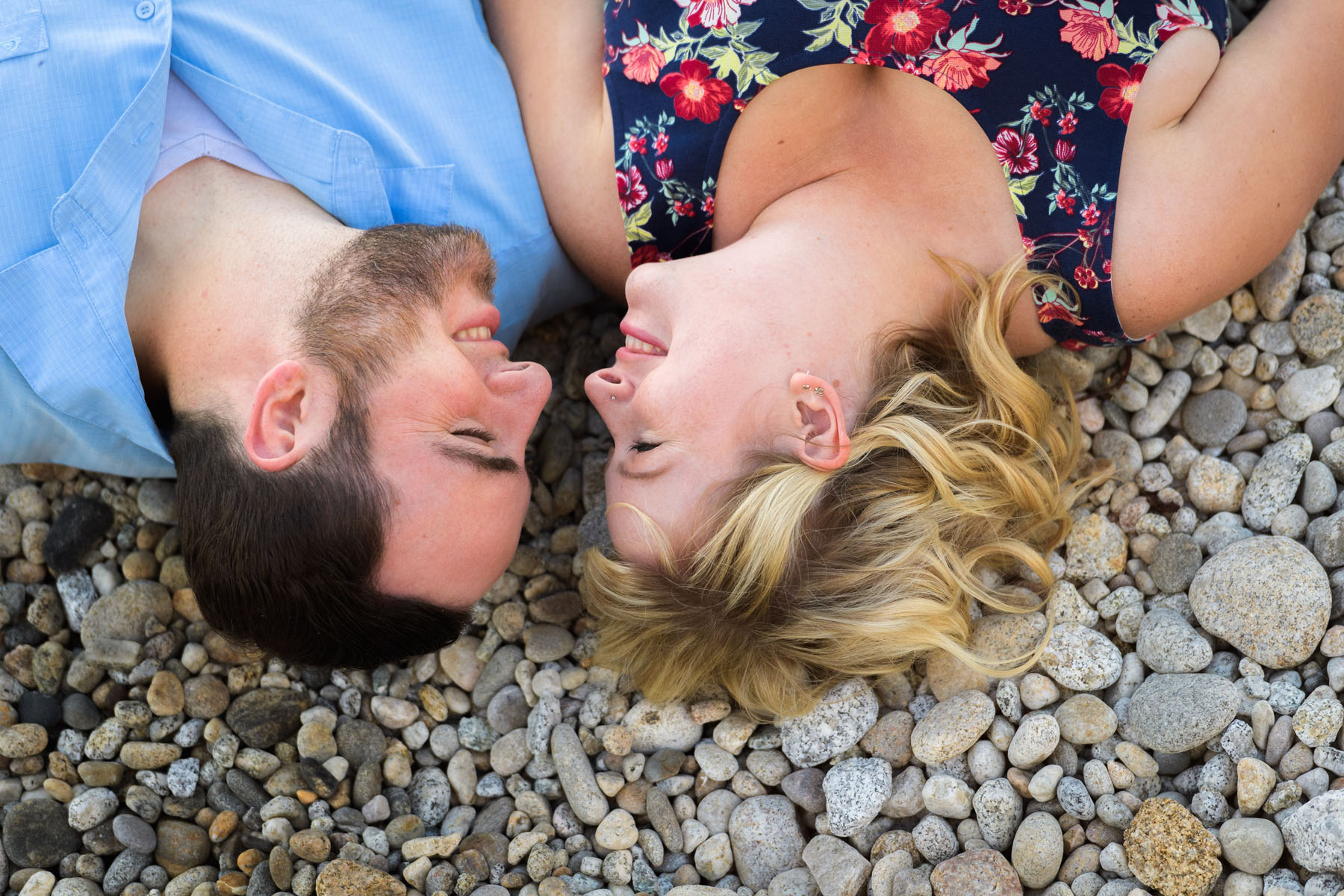 couple laying on beach facing each other - Stewart's Cove - Carmel Engagement Photography - photos by Bay Area wedding photographer Chris Schmauch