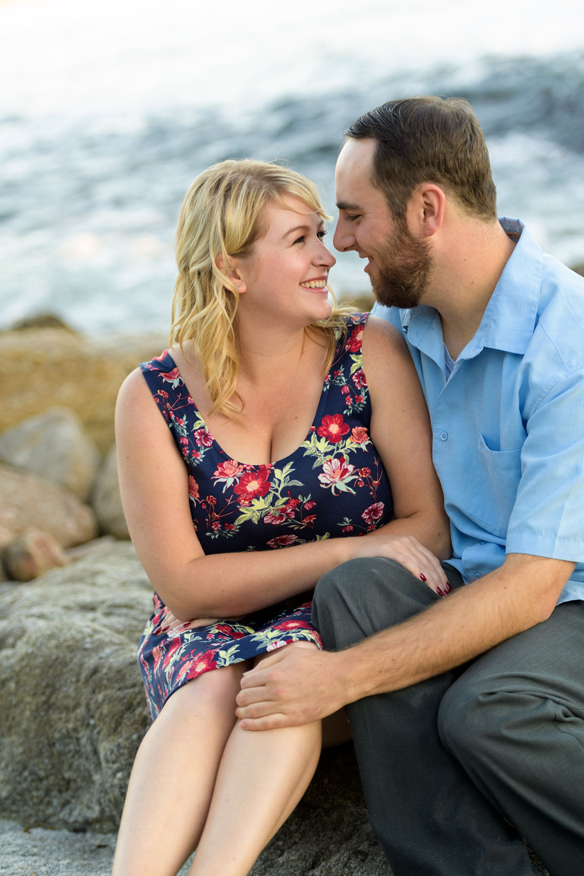 couple sitting on beach rock cuddling - Stewart's Cove - Carmel Engagement Photography - photos by Bay Area wedding photographer Chris Schmauch