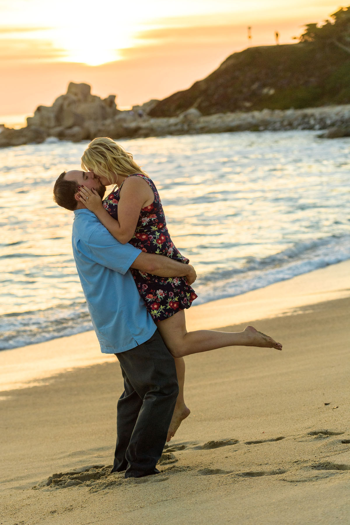 lifting his fiance up and kissing on beach at sunset - Stewart's Cove - Carmel Engagement Photography - photos by Bay Area wedding photographer Chris Schmauch