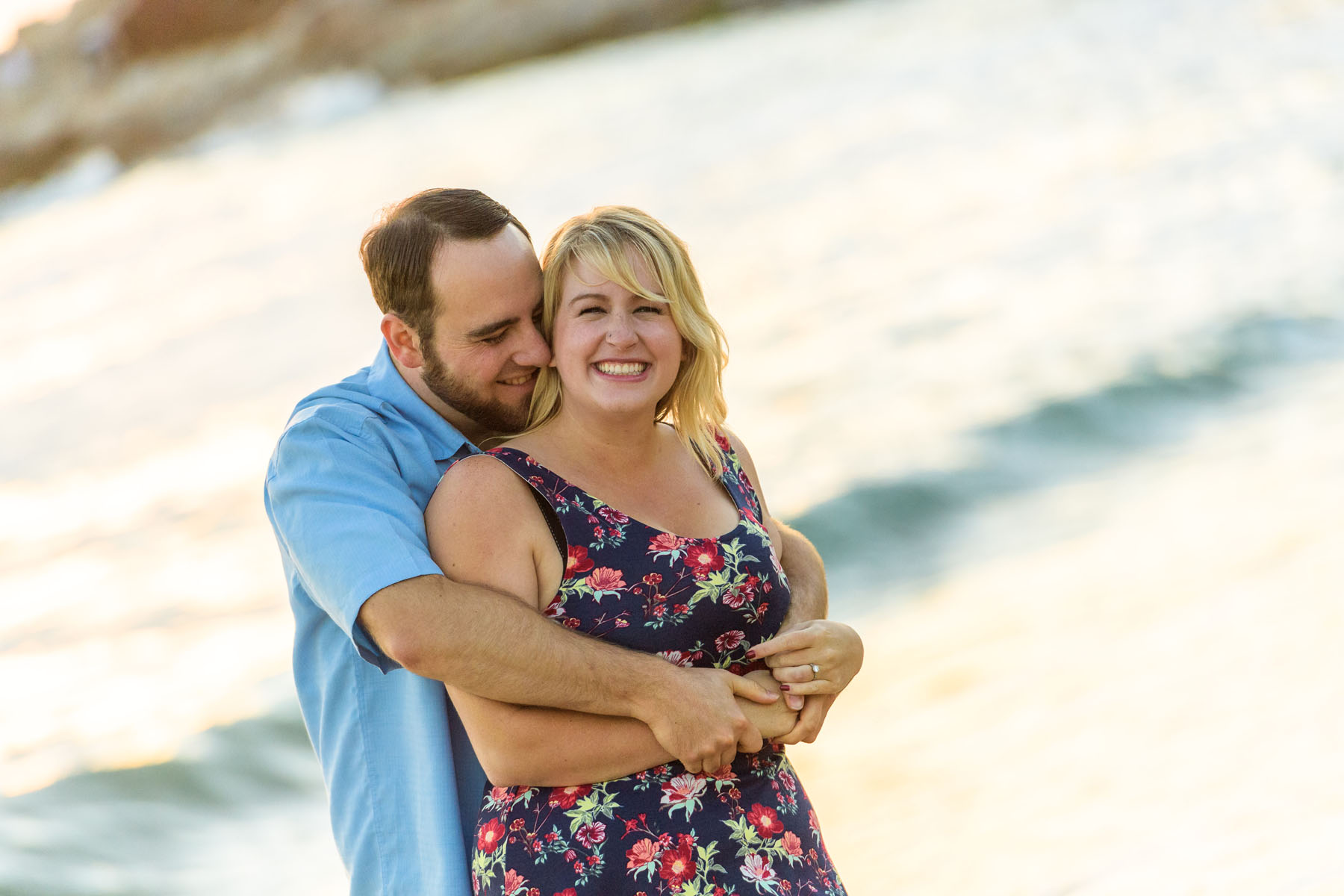 he hugs her from behind on the beach - Stewart's Cove - Carmel Engagement Photography - photos by Bay Area wedding photographer Chris Schmauch